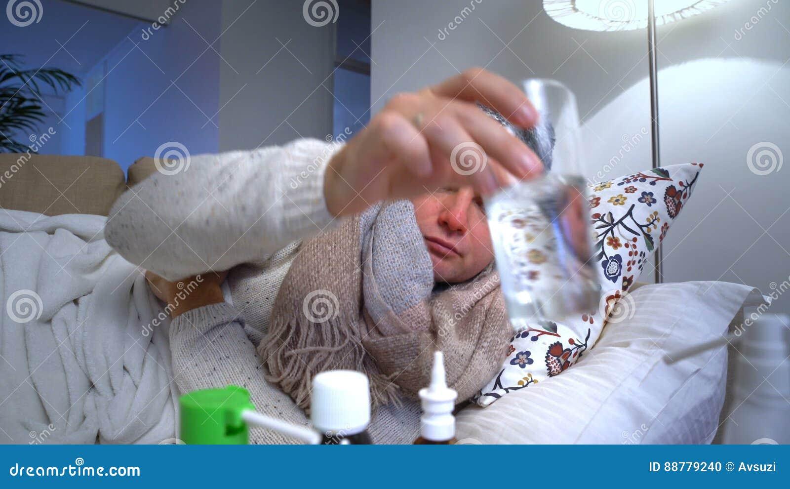 Kranker Mann, der eine warme Kappe und einen Schal in der Bett-Husten-und Maß-Temperatur trägt stock footage