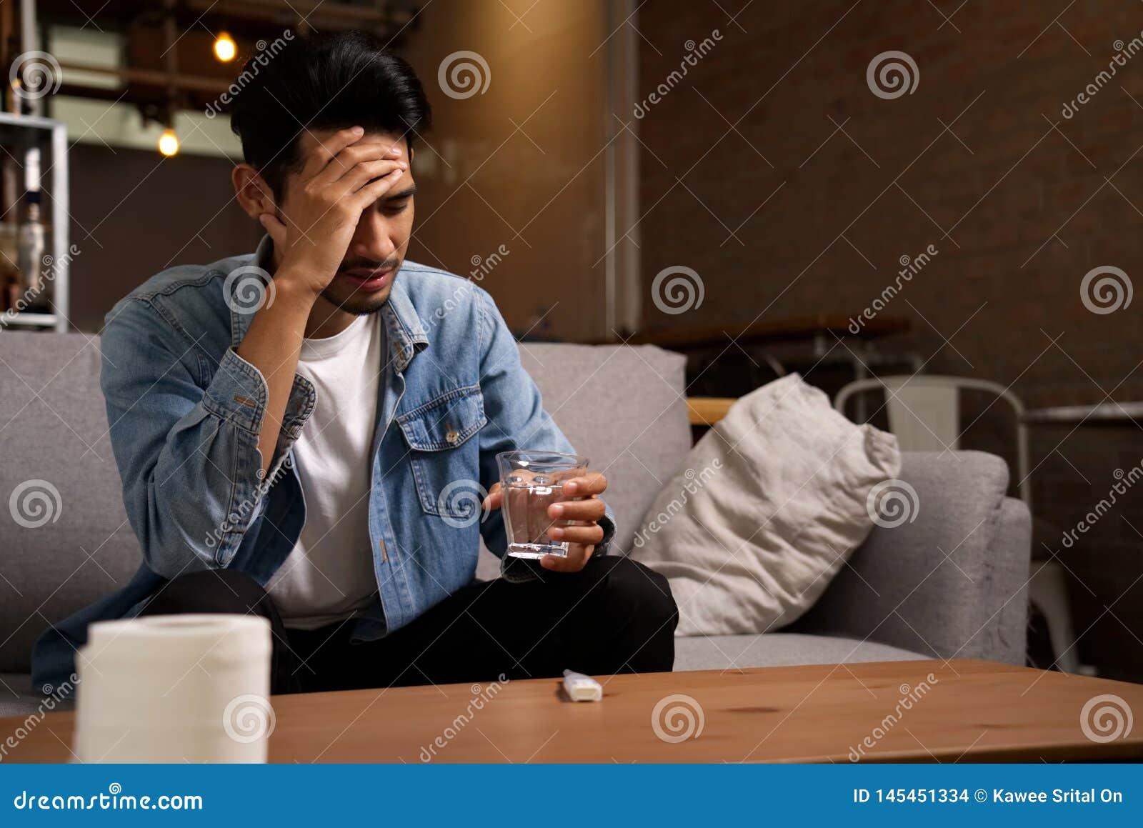 Krankheit und ungesundes Bedingungskonzept Kopfschmerzenmann, der auf Sofa sitzt