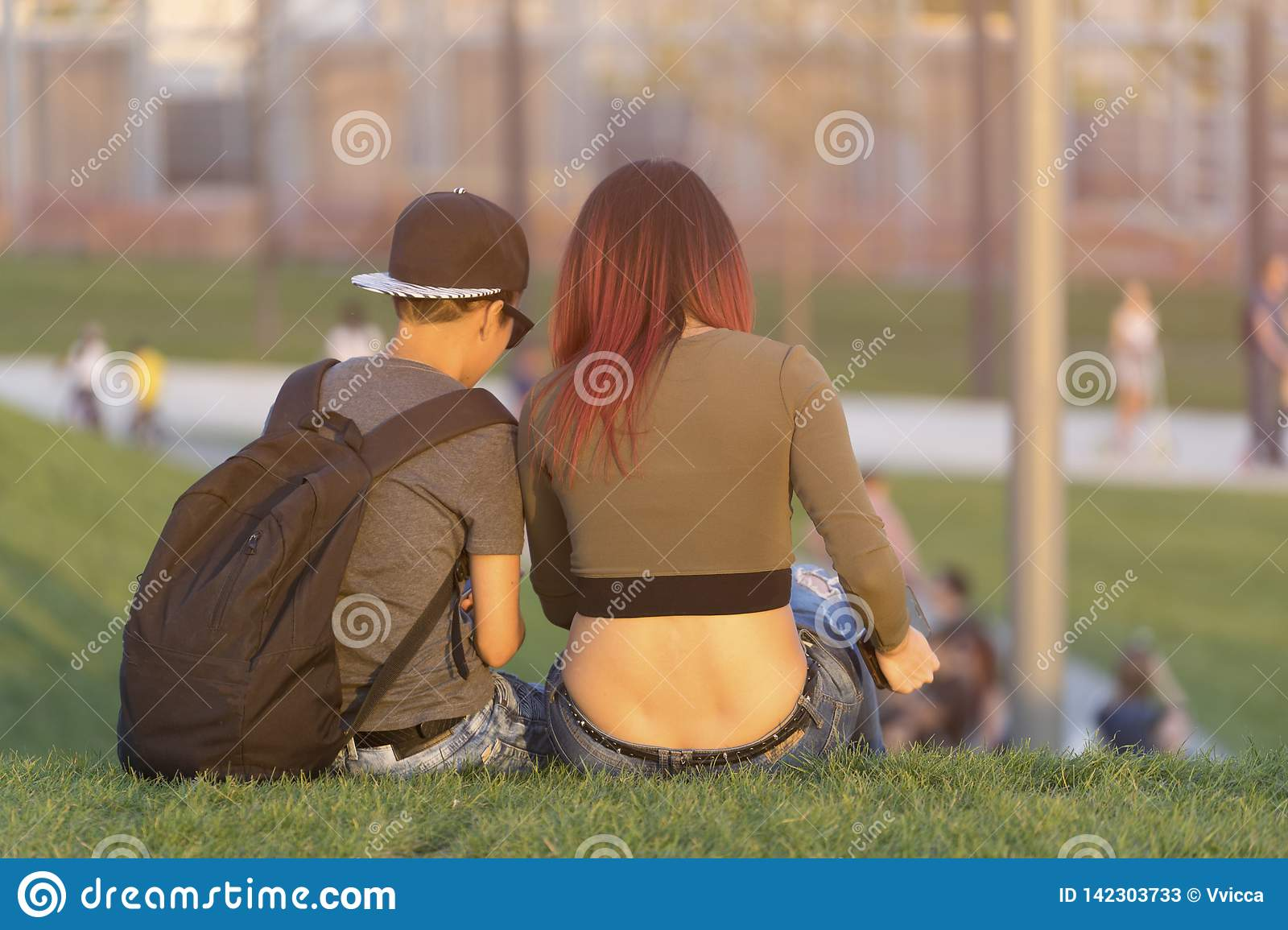 Young Man and girl sitting with their backs on the green grass