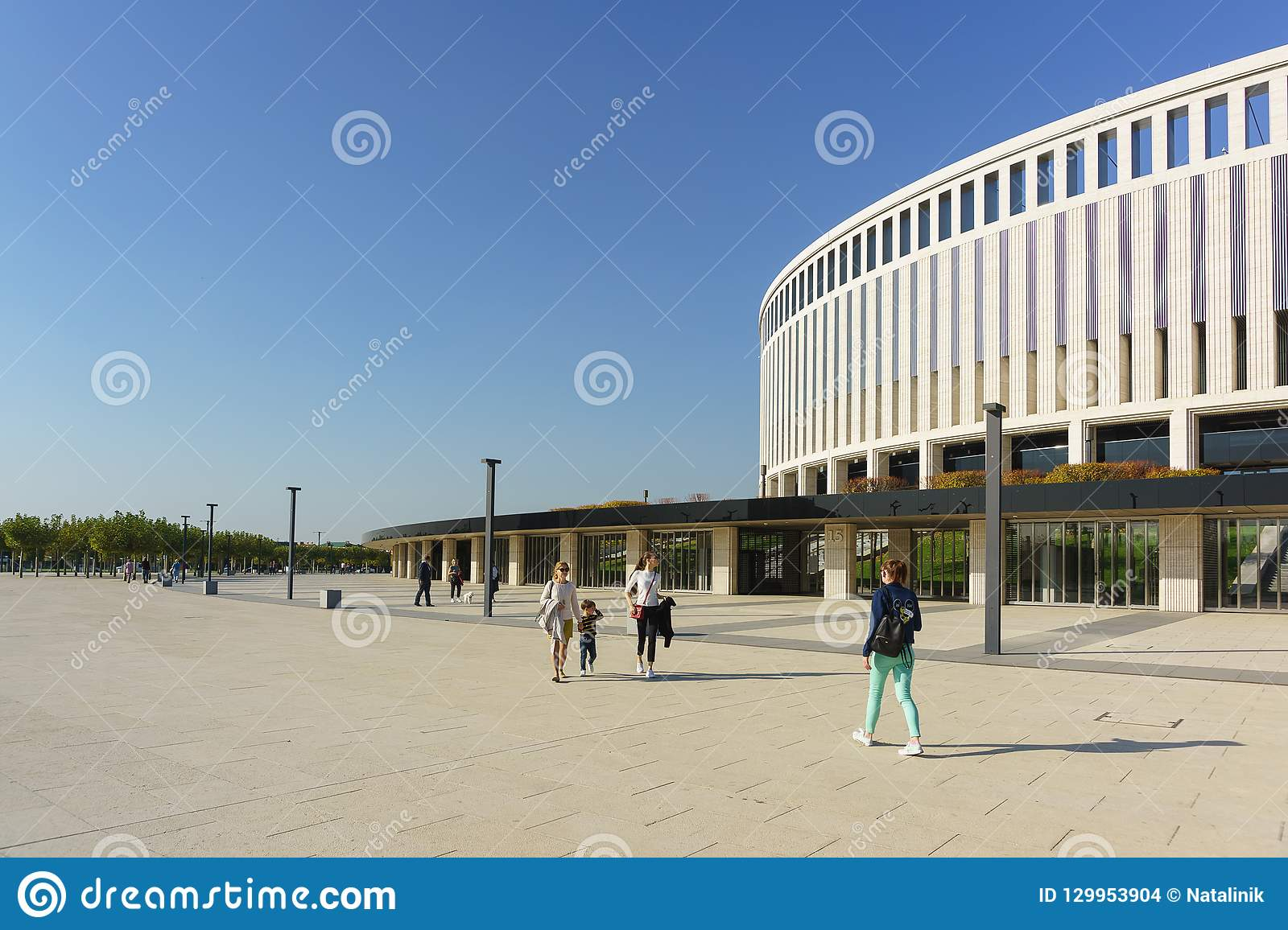People walk past the modern capacious stadium of FC Krasnodar on a Sunny day. A large area in front of the building is designed fo