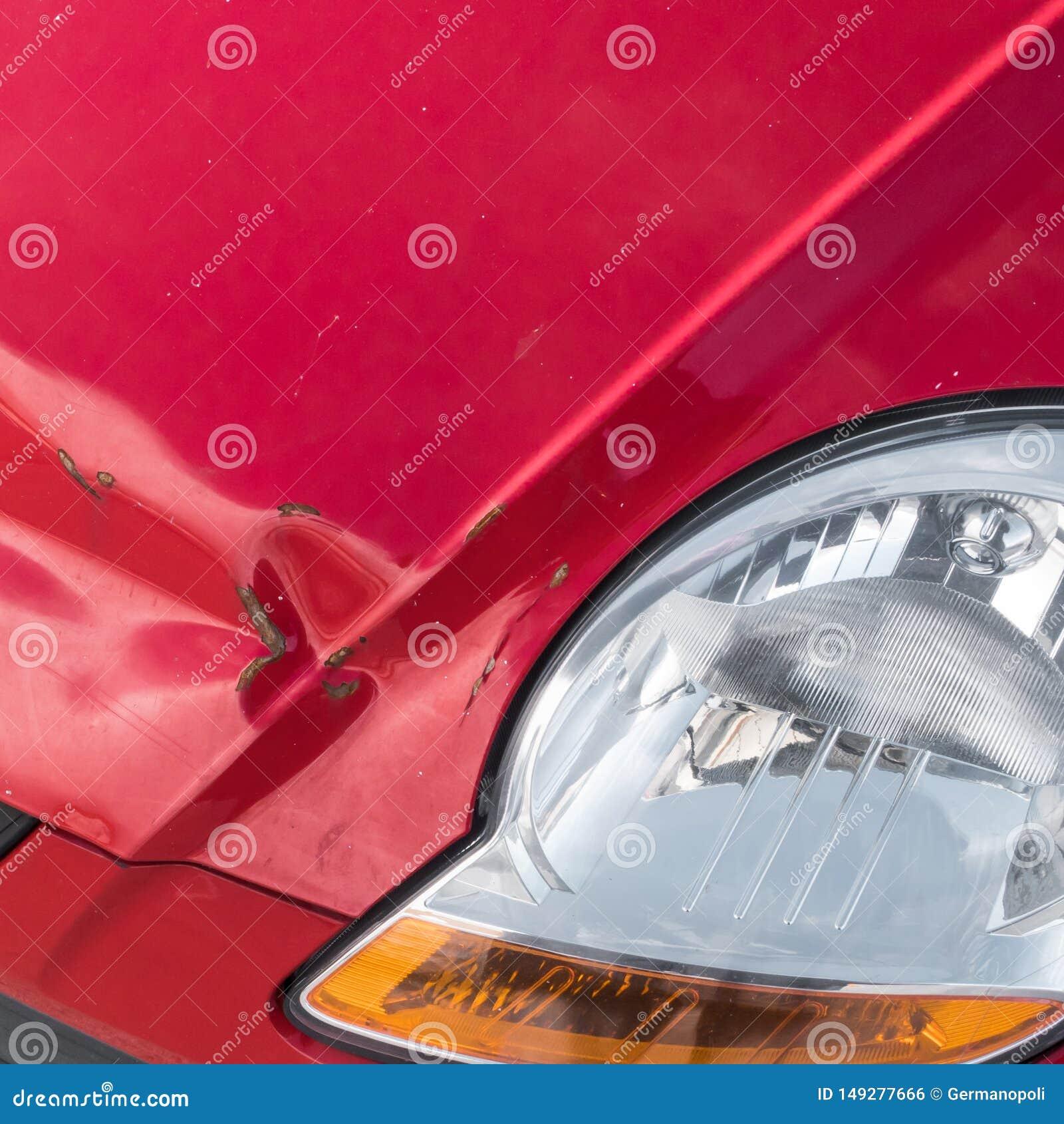 Kratzer und rostige Einbuchtung auf Front des roten Autos