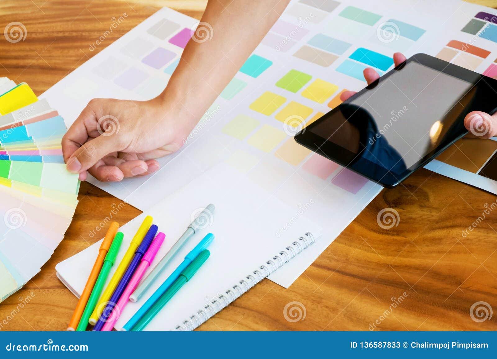 Kreative Geschäftsfrau unter Verwendung der Tablette und Arbeiten an Farbtafeln auf Schreibtisch in einem modernen Büro