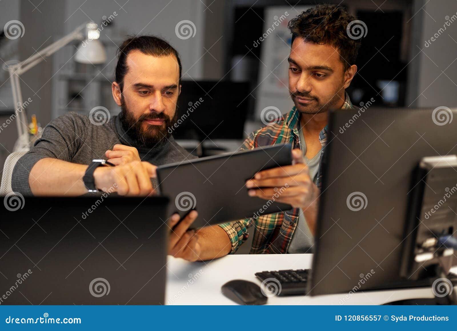 Kreatywnie drużyna z pastylka komputerem osobistym pracuje przy biurem