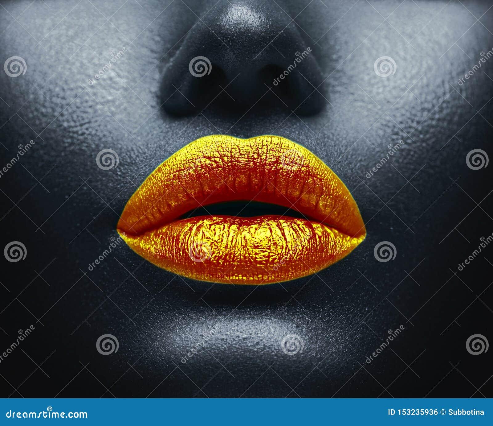 Kreatywnie kolorowy makeup Bodyart, lipgloss na seksownych wargach, dziewczyny usta Złote wargi na czarnej skórze