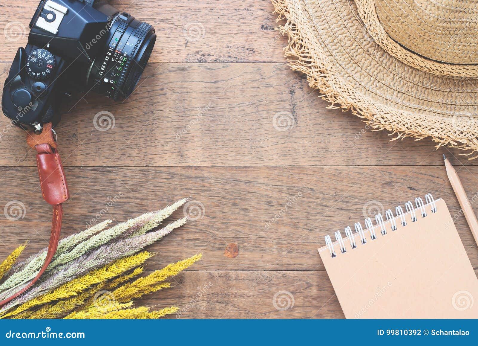 Kreatywnie mieszkanie nieatutowy jesieni pojęcie z wysuszonymi kwiatami, kamerą, słomianym kapeluszem i notatnikiem na drewnie,