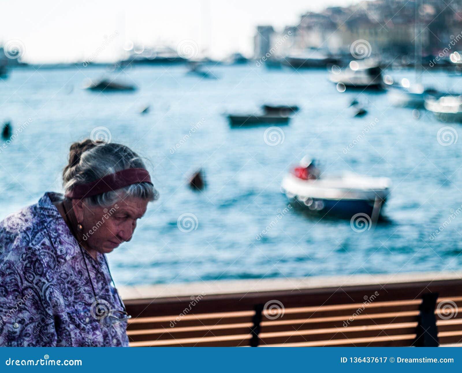 Kreatywnie scena stara kobieta od Rovinj, Chorwacja środkowy Europa w midday, z pięknymi łodzi bokeh piłkami pożytecznie dla prób