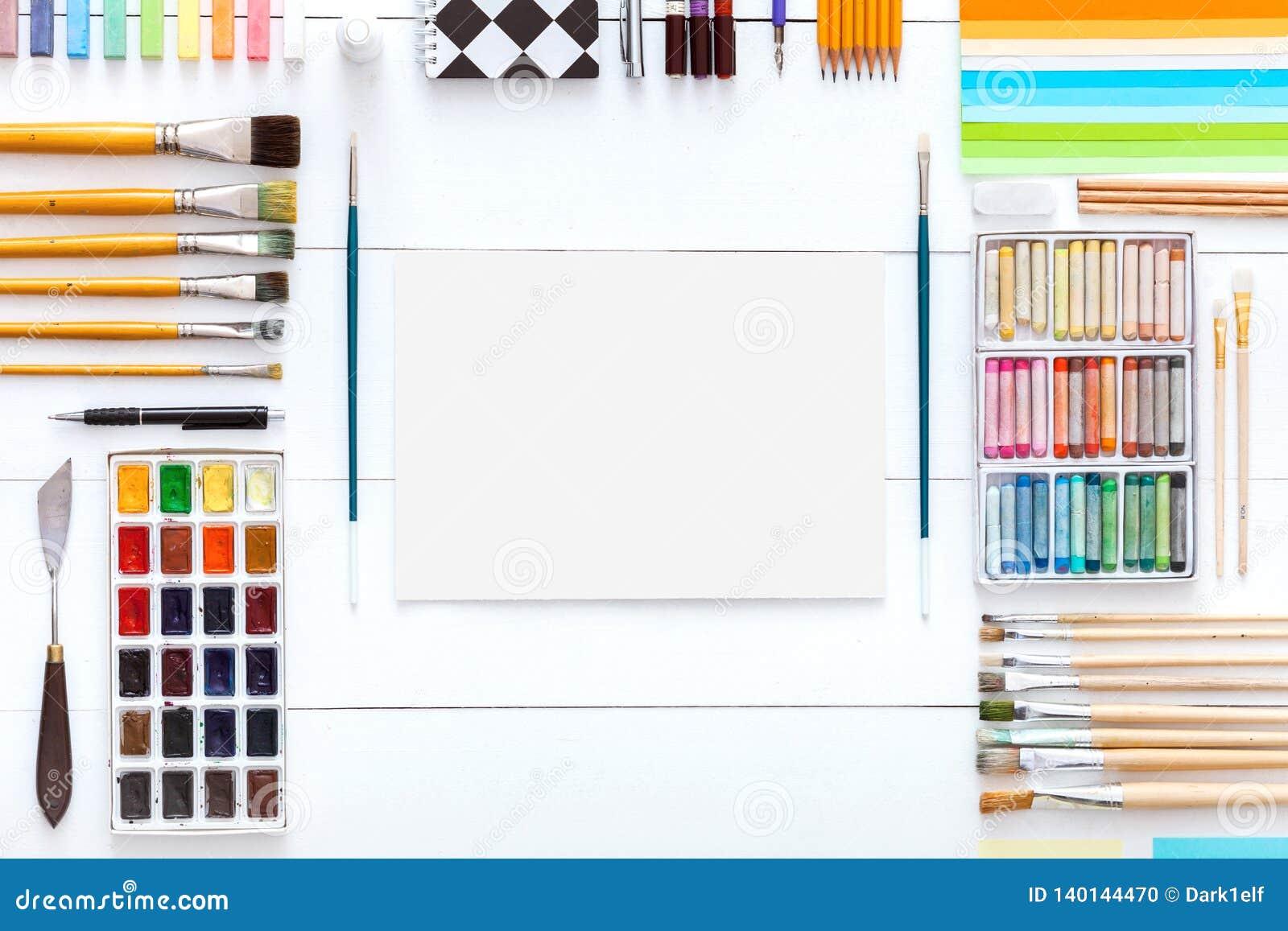 Kreatywnie uczenie pojęcie, różnych dostaw kolorowi akcesoria ustawiający dla sztuki pracy na białym drewnianym tle, paintbrushes
