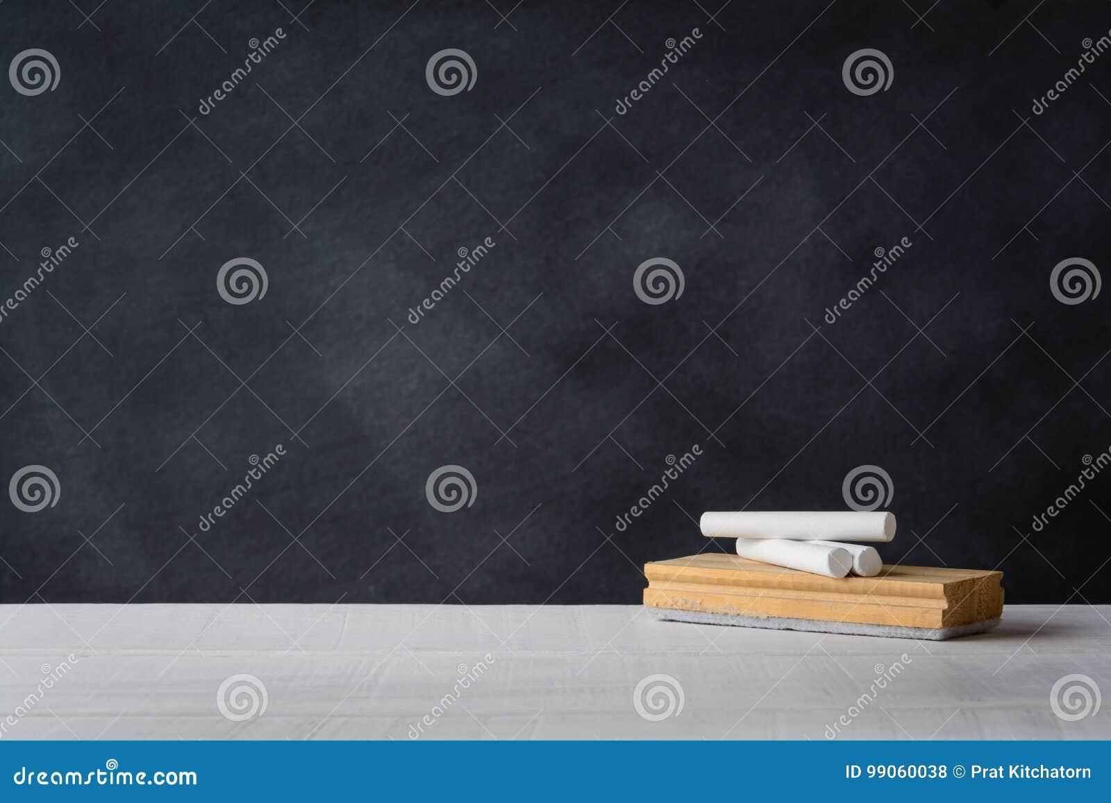 Kreda i gumka wsiadamy na białym biurku Blackboard tło