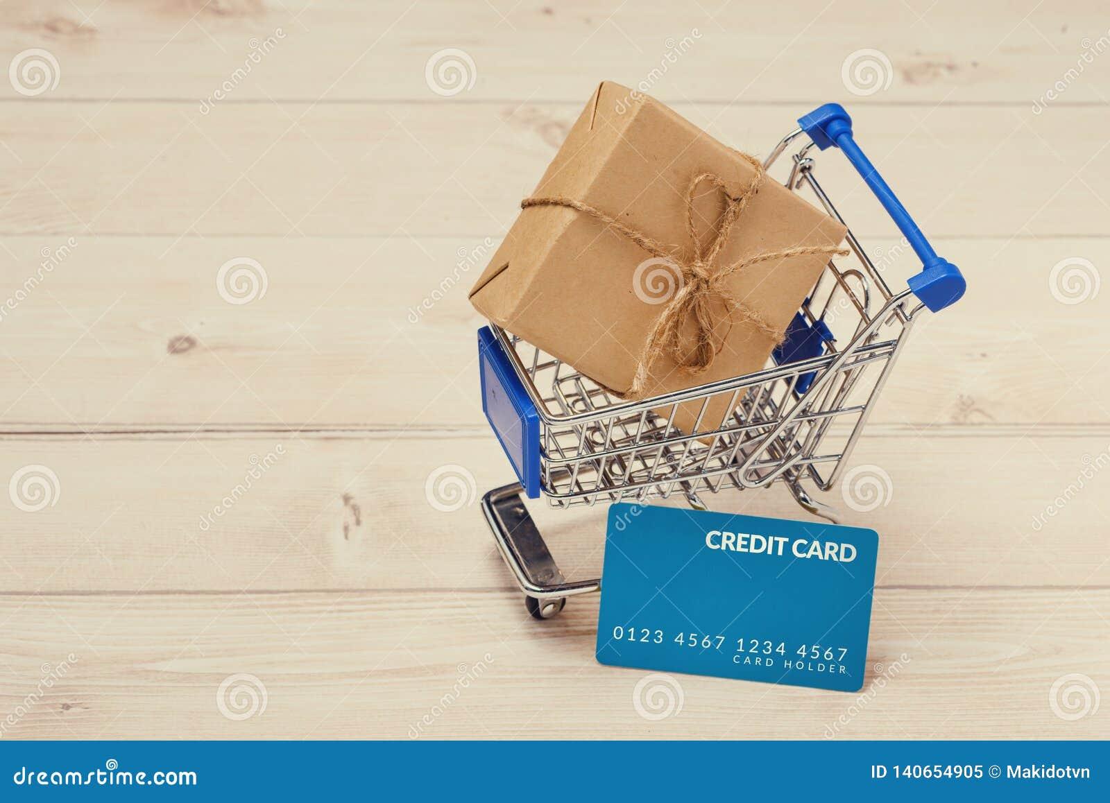 Kreditkort och shoppingvagn med gåvaasken som slås in med papper kraft på tabellen