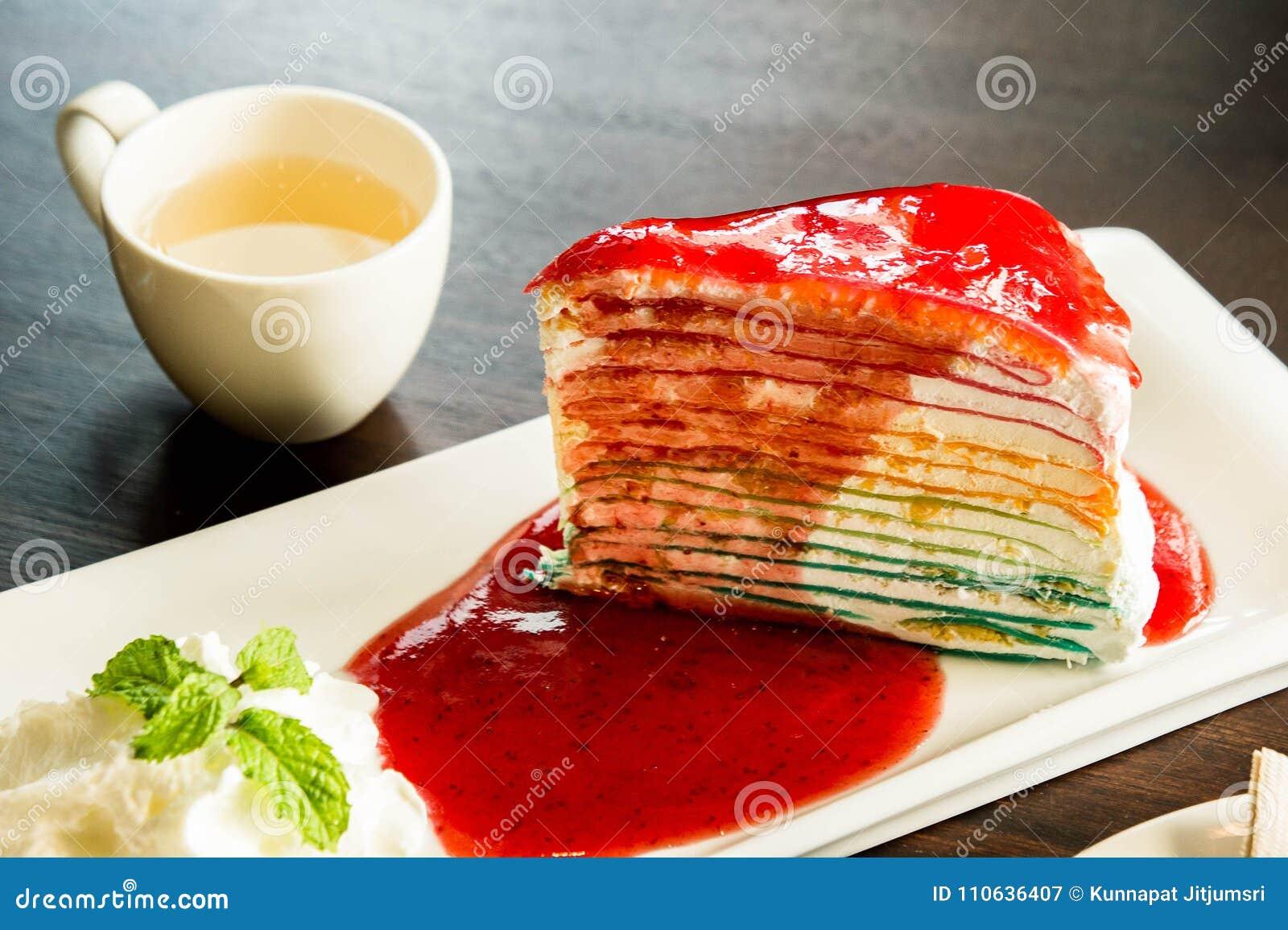 Kreppkuchenschicht-Regenbogenfarbe und Soßenerdbeernachtisch auf Tellerweiß im Café