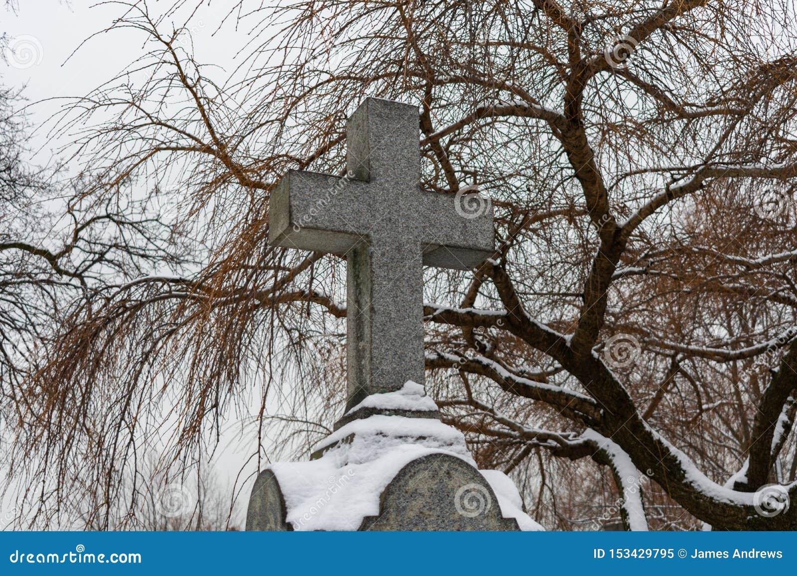 Kreuz auf eine Finanzanzeige an einem Kirchhof im Winter mit Schnee