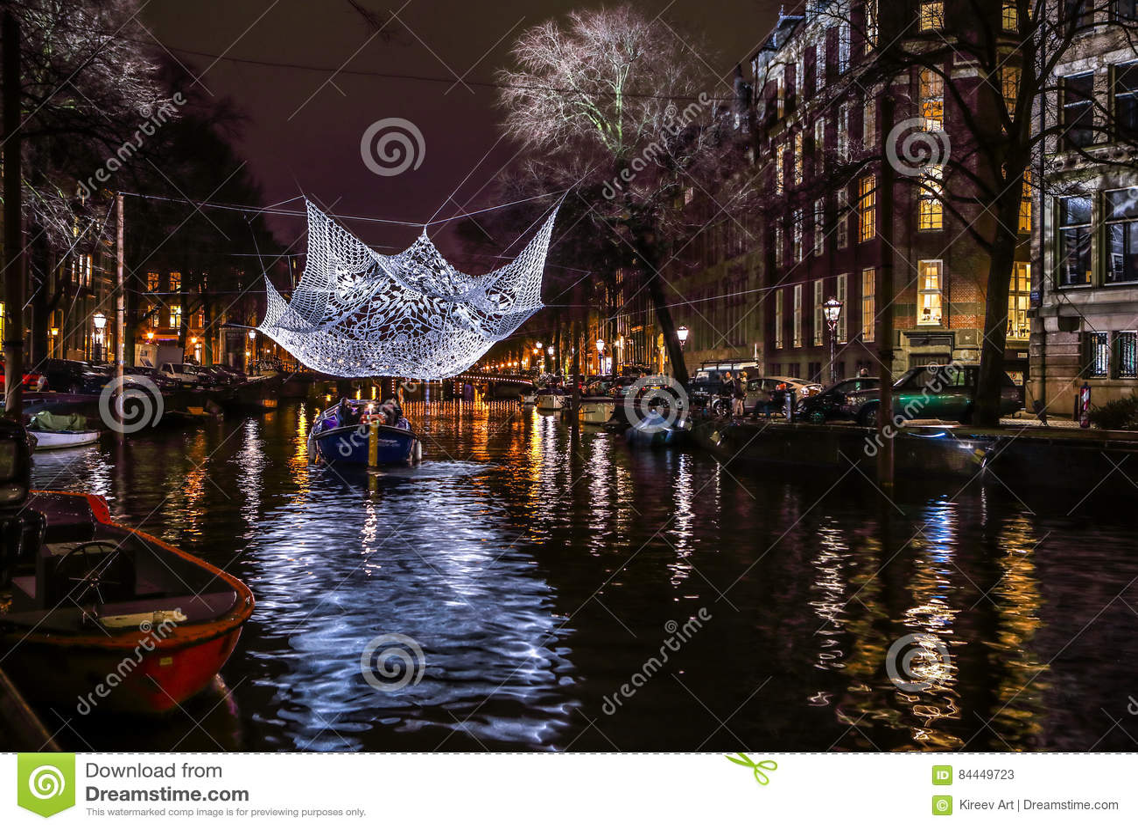 Kreuzfahrtbootseile in den Nachtkanälen Helle Installationen auf Nachtkanälen von Amsterdam innerhalb des hellen Festivals