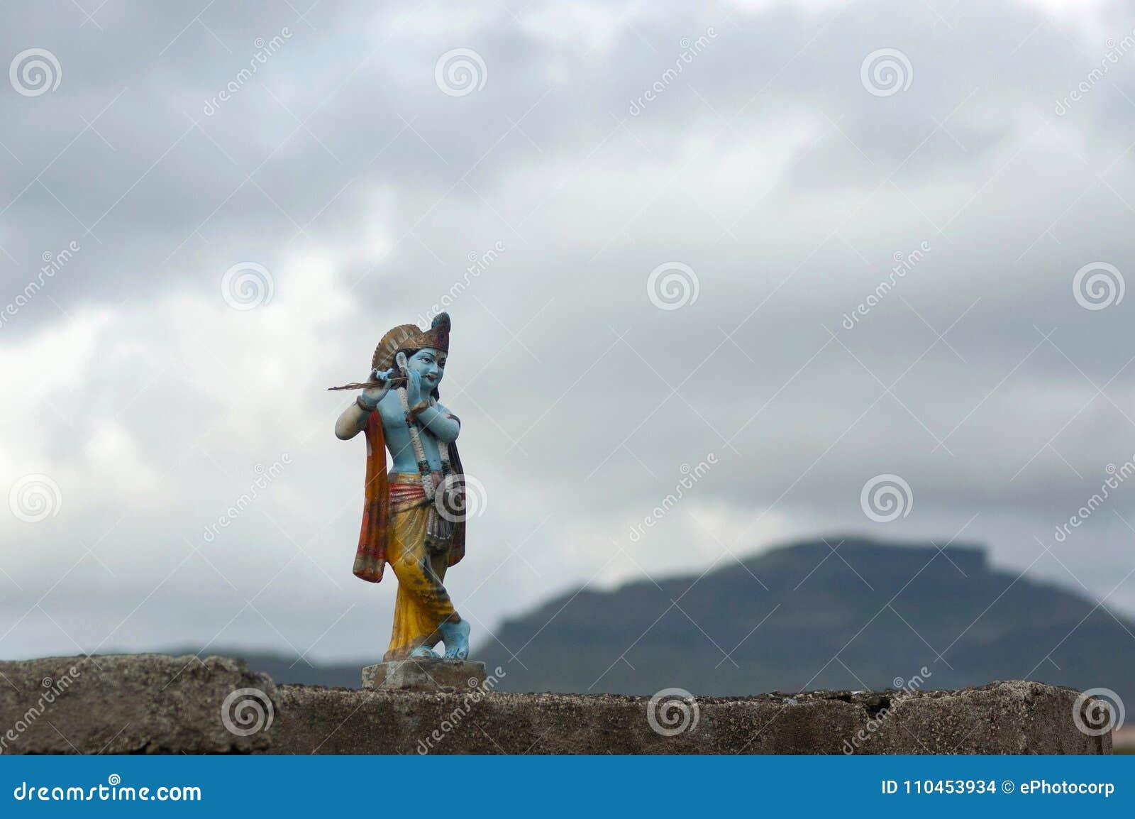 Krishna Idol med bakgrund för molnig himmel