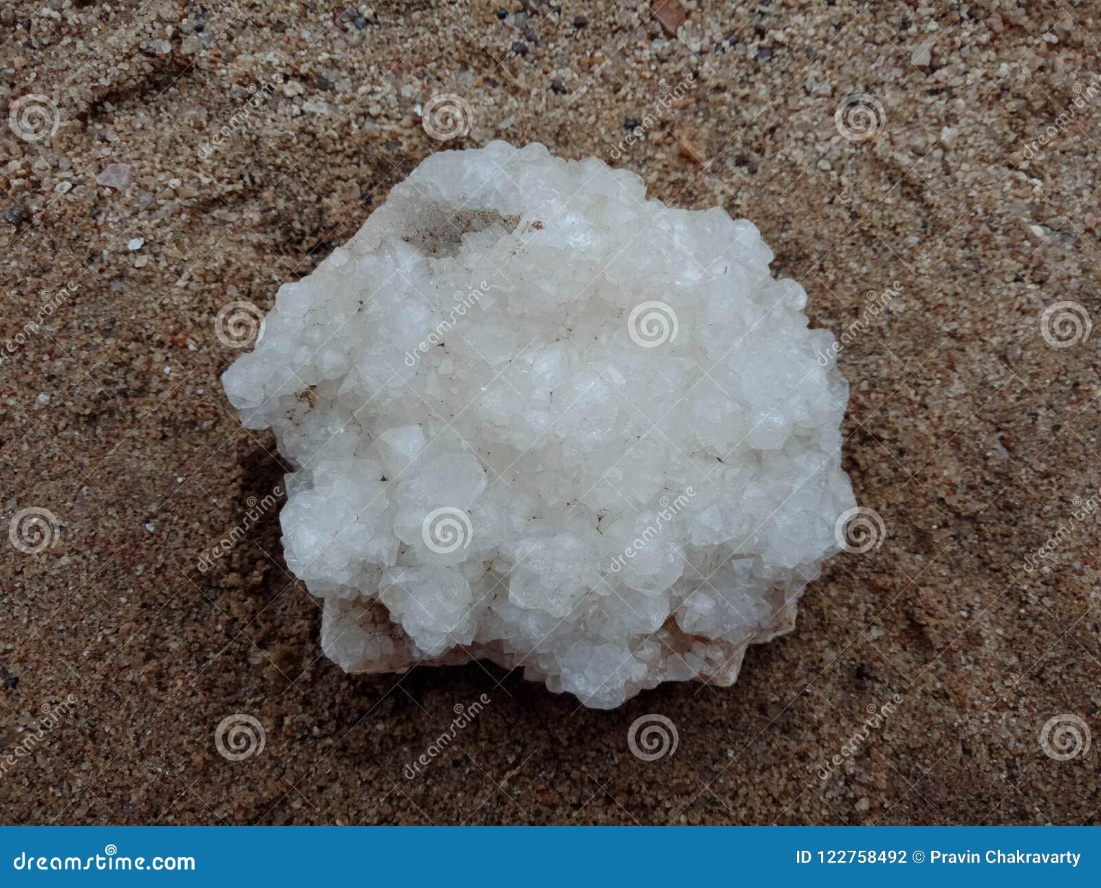 Kristalsteen op het zand, geweven achtergrond natuursteen, zeldzame halfedel behang, overzees, oceaan