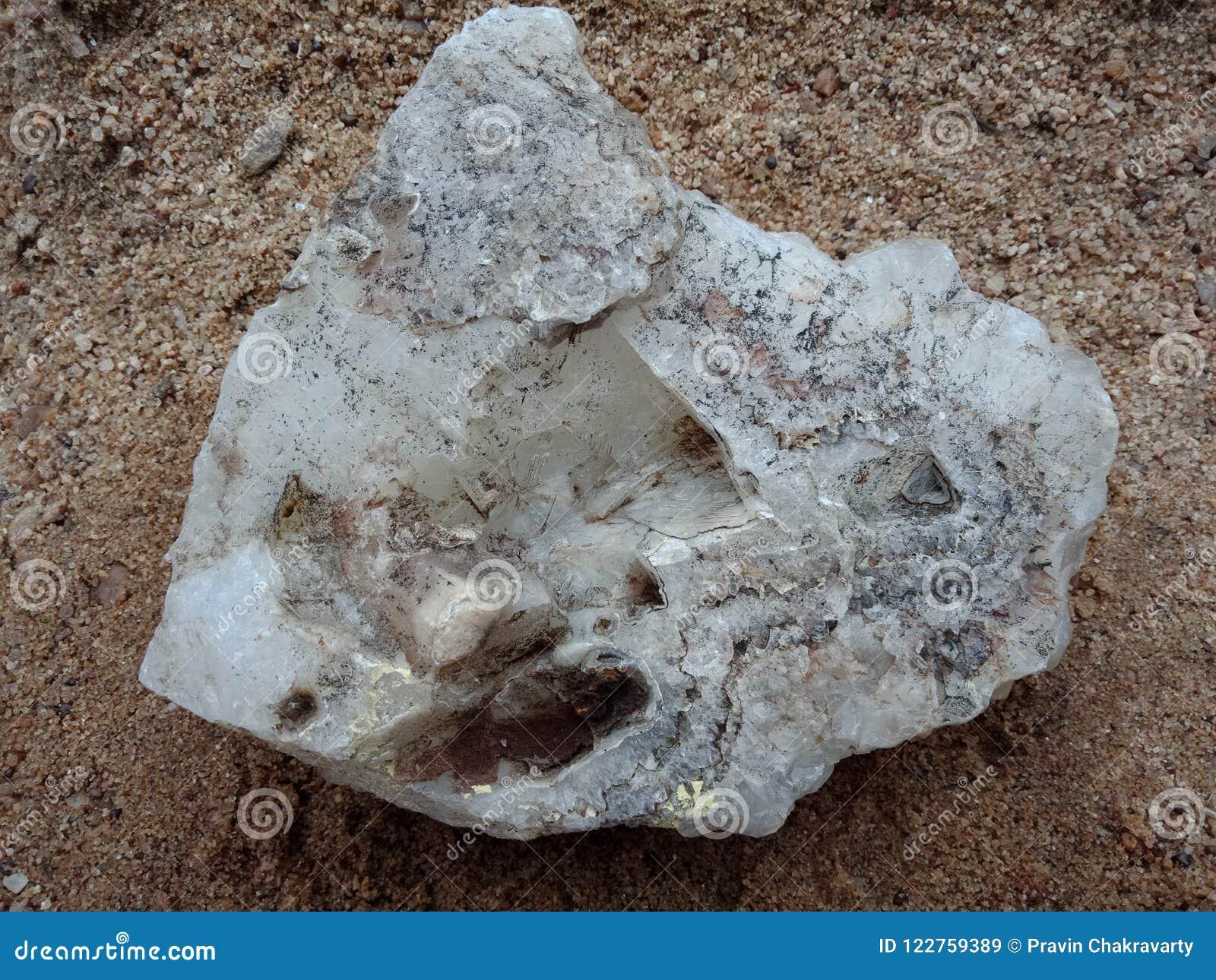 Kristalsteen op het zand, geweven behang als achtergrond