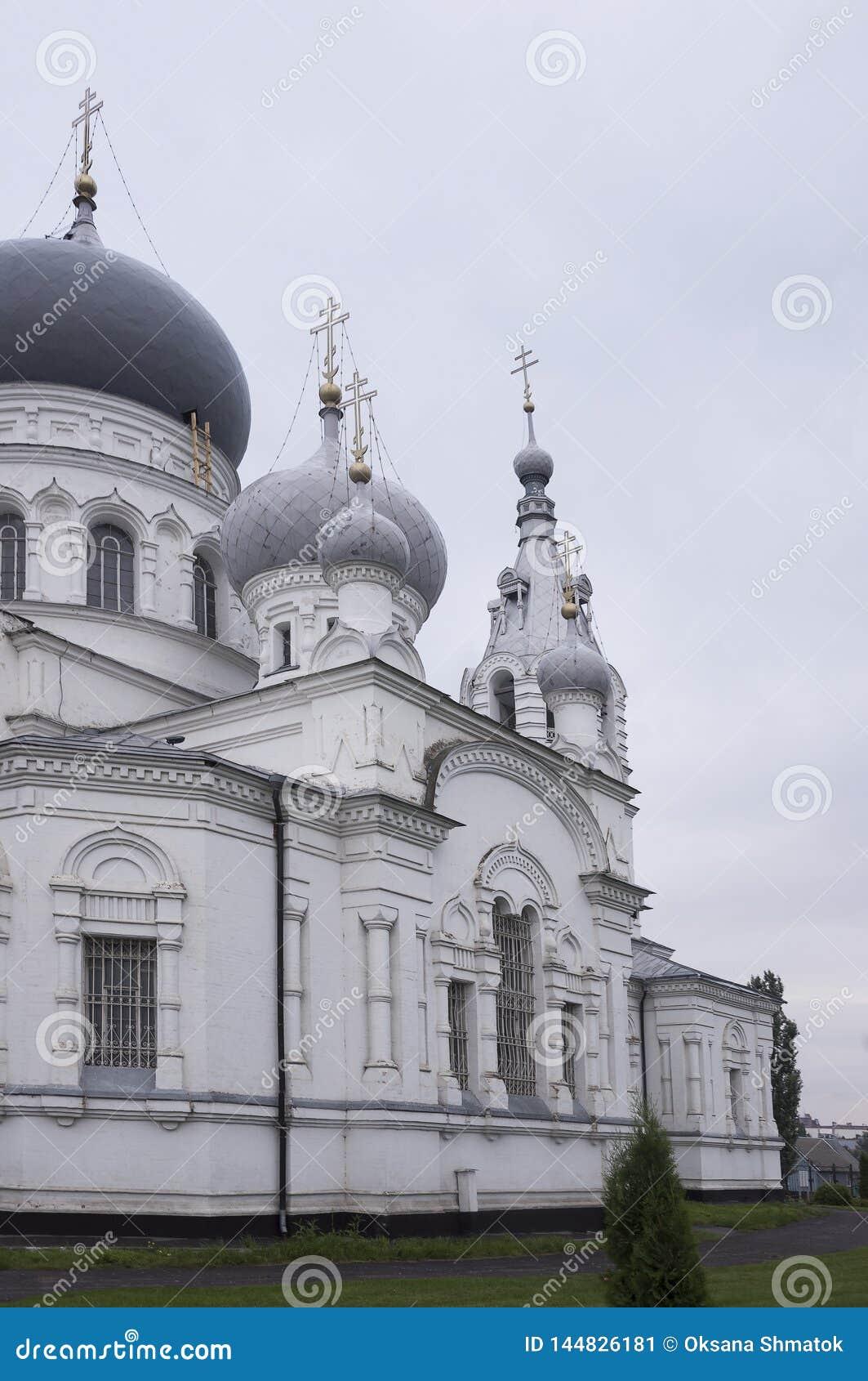 Kristen ortodox vit kyrka med silver och gråa kupoler med guld- kors Lugna grå himmel över