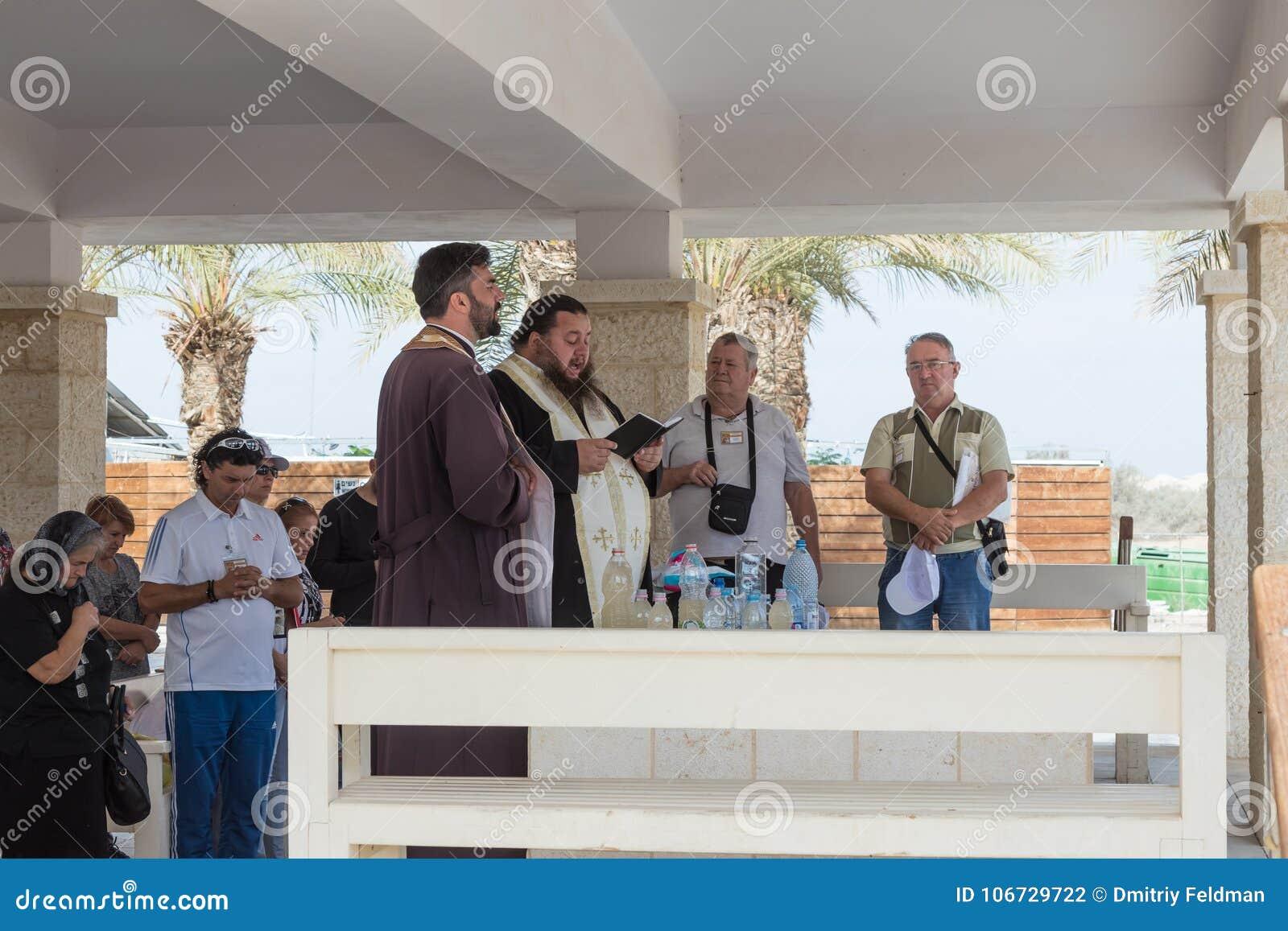 Kristna präster ber i närvaron av troenden på den turist- platsen Qasr el Yahud i Israel