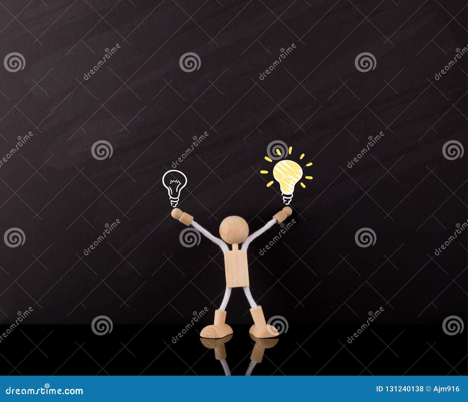 Kritisches denkendes Fähigkeits-Konzept, hölzerne Stock-Zahl Arme oben, große gelbe Glühlampeskizze, auf einer Tafel