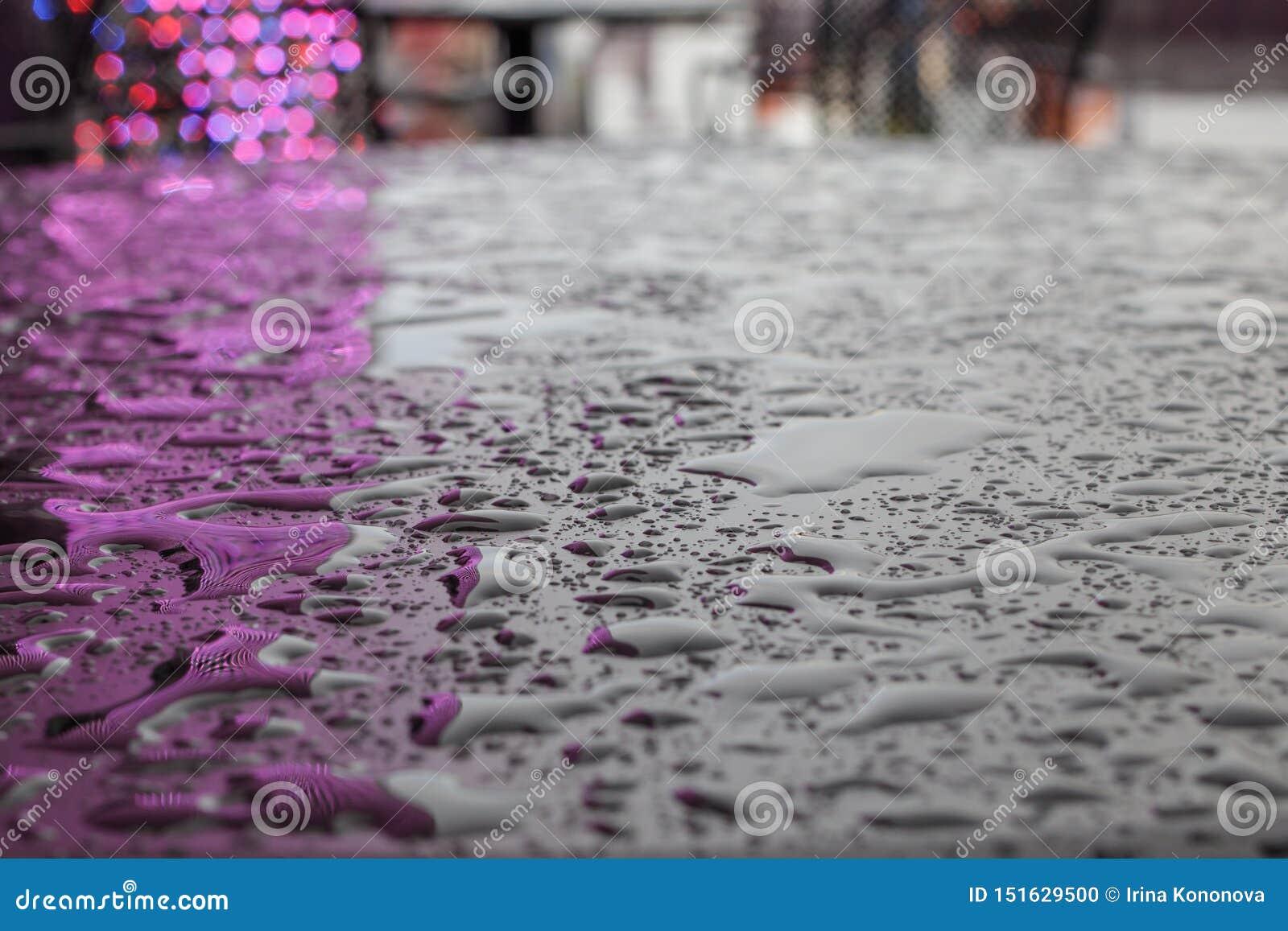 Krople lub małe kałuże woda po tym jak deszcz na gładkiej matte powierzchni ciemny kolor, odbija światła iluminacja