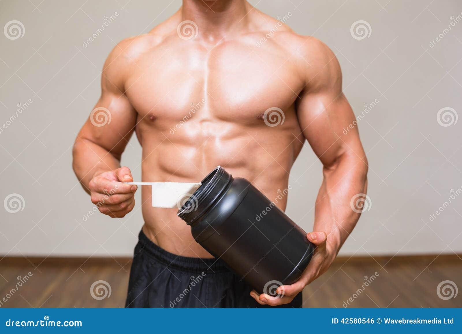 Kroppbyggmästare som rymmer en skopa av proteinblandningen i idrottshall