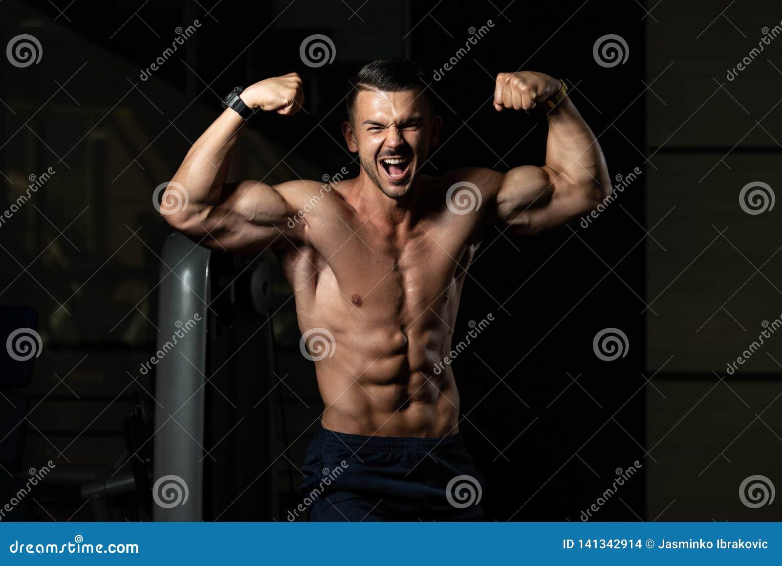 Kroppsbyggare som b?jer den Front Double Biceps Pose In idrottshallen