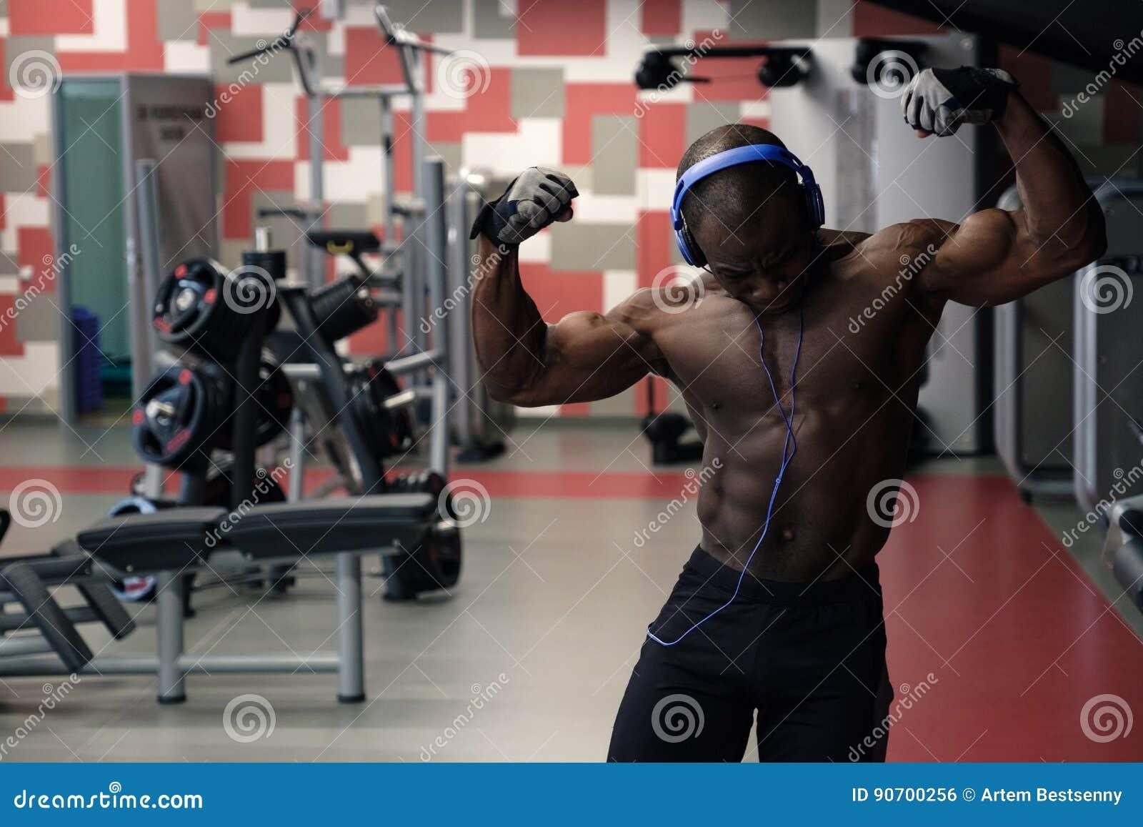Kroppsbyggareman som poserar i idrottshallen