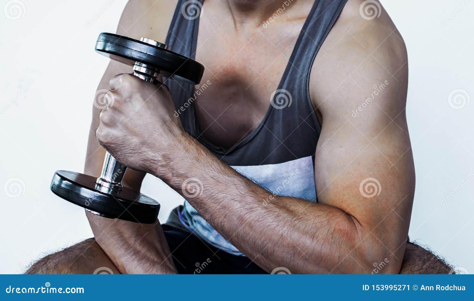 Kroppsdel och muskel av en man med hanteln