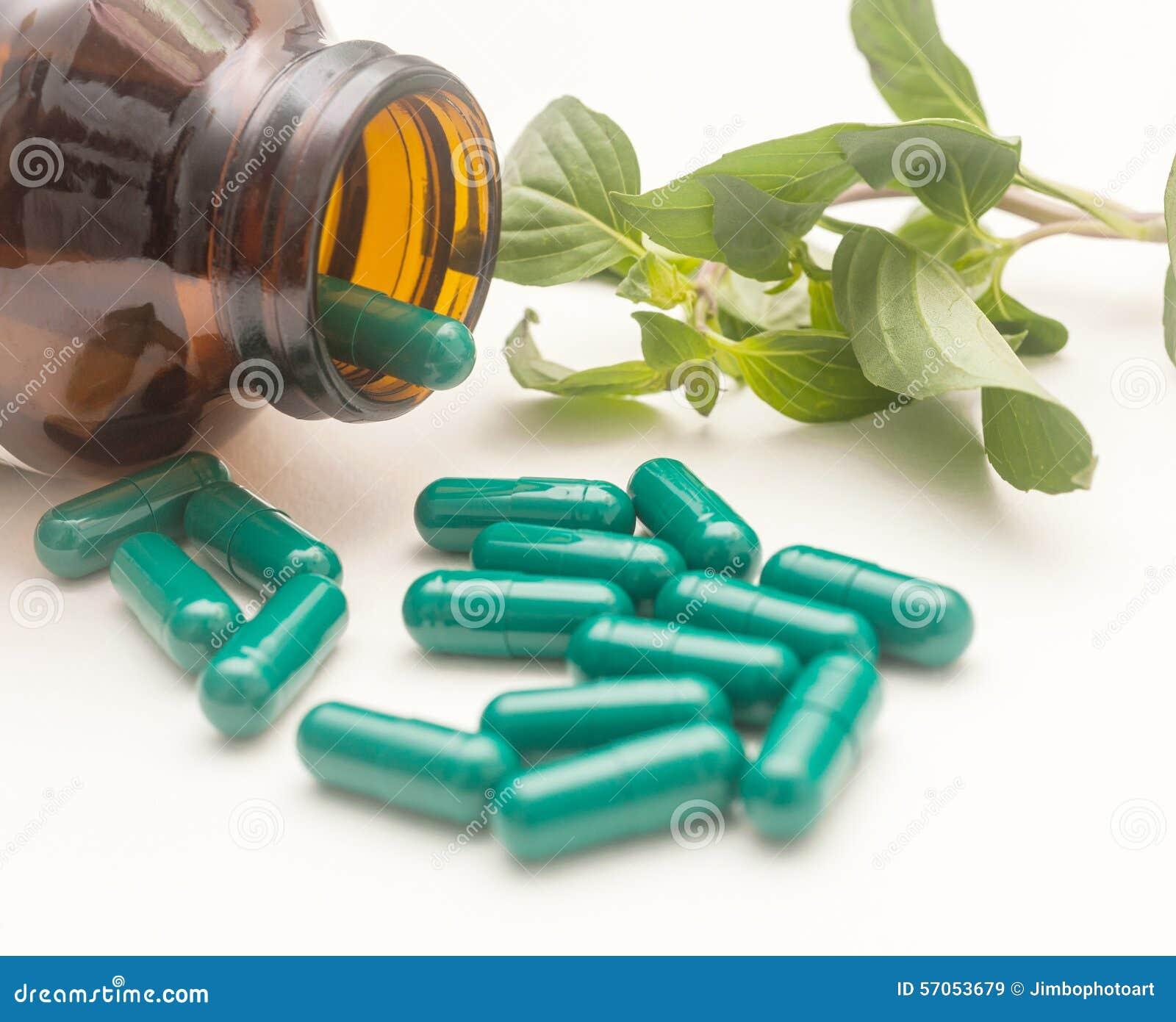 Kruid in groene capsule die uit een fles morsen