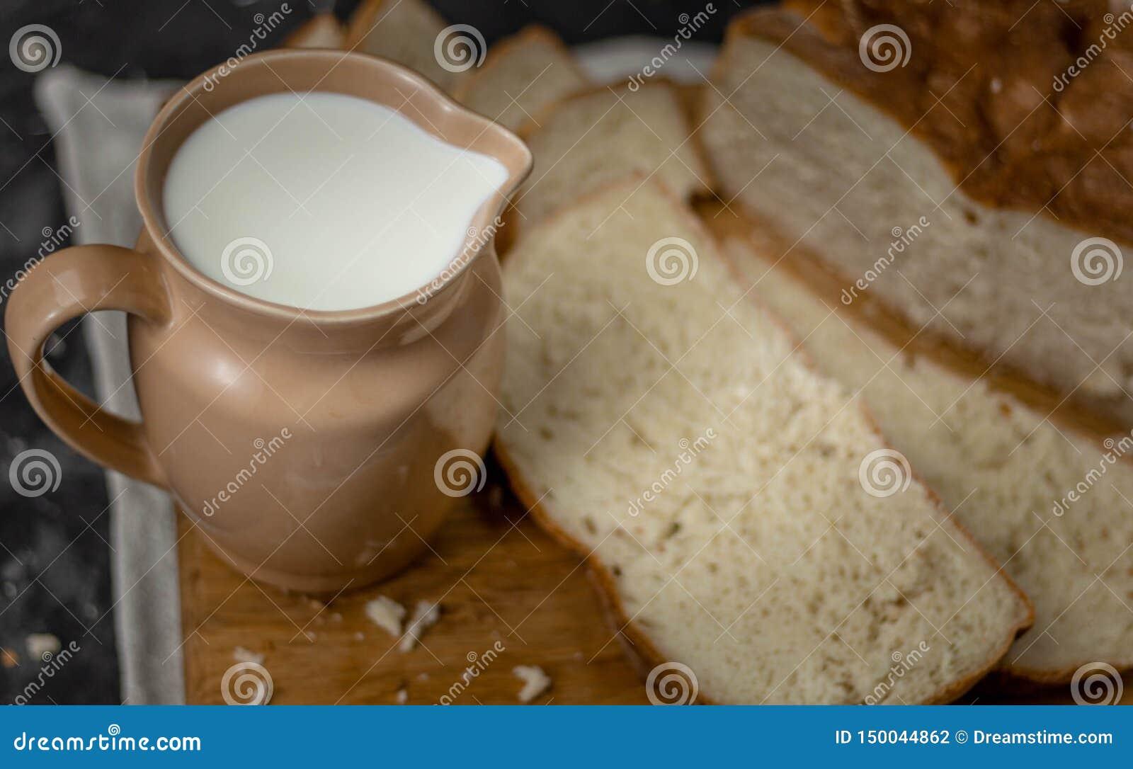 Kruik melk en een brood van brood op een houten raad