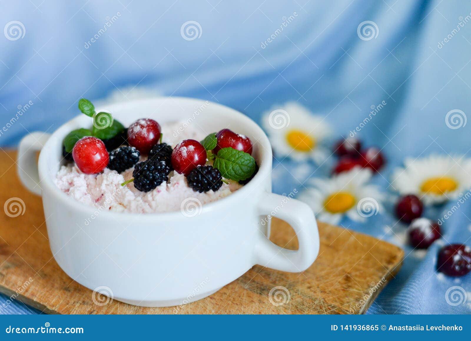 Kruiken natuurlijke witte yoghurt met fruitsalade met roze draakfruit, bessen en munt op houten lijst Het gezonde Eten