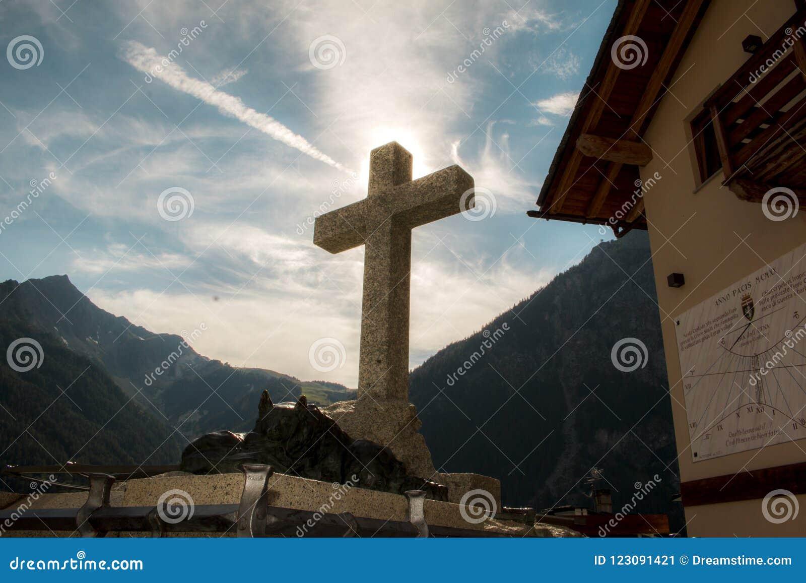 Kruis met zon en bergen op achtergrond