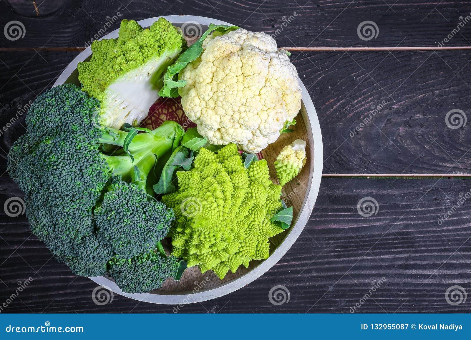 Kruisbloemige groenten Romanesco, bloemkool en broccoli op een rond dienblad op een houten achtergrond Vlak leg Hoogste mening