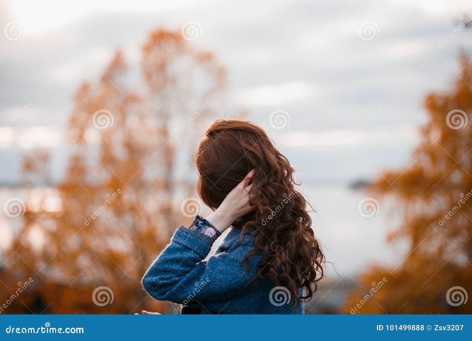 Krullend haar mooi jong Kaukasisch meisje die in openlucht blauwe laag dragen, die in de herfstpark stellen