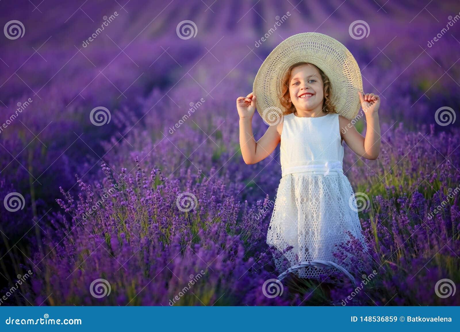 Krullend meisje die zich op een lavendelgebied in witte kleding en hoed met leuk gezicht en aardig haar met lavendelboeket bevind