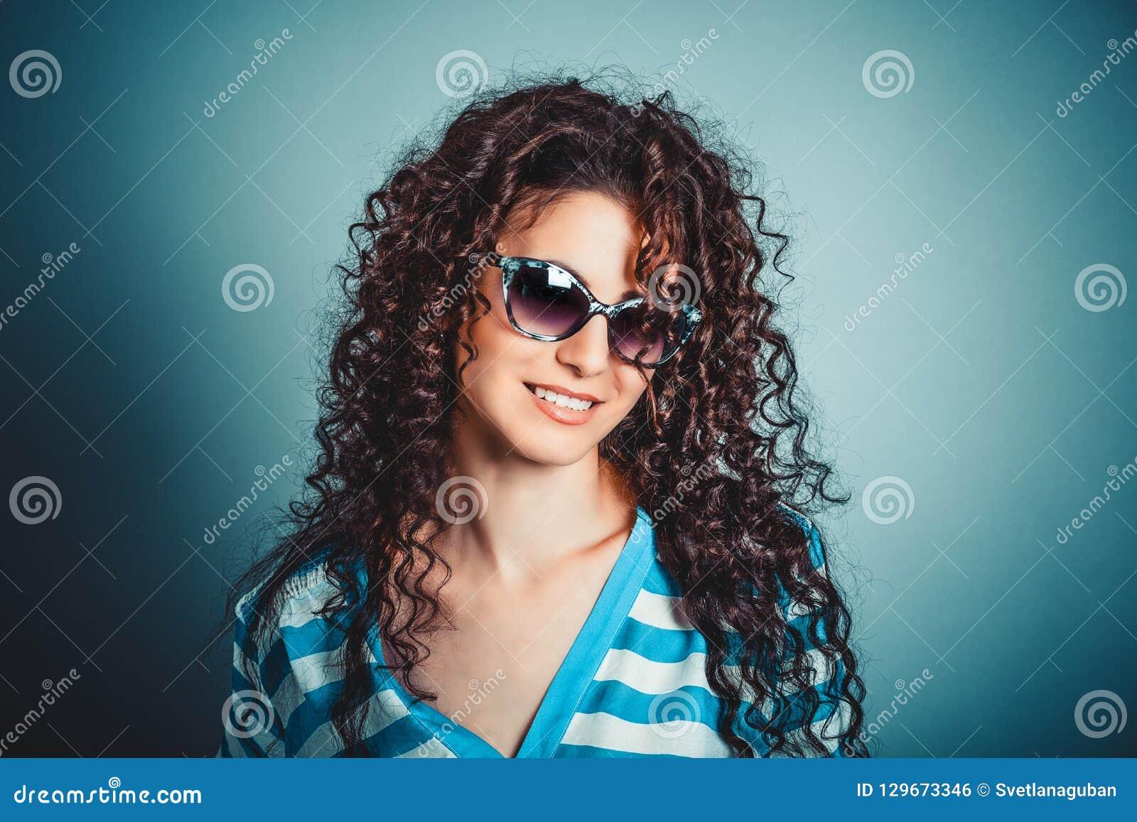 Krullend vrouwenmeisje in zonnebril het glimlachen