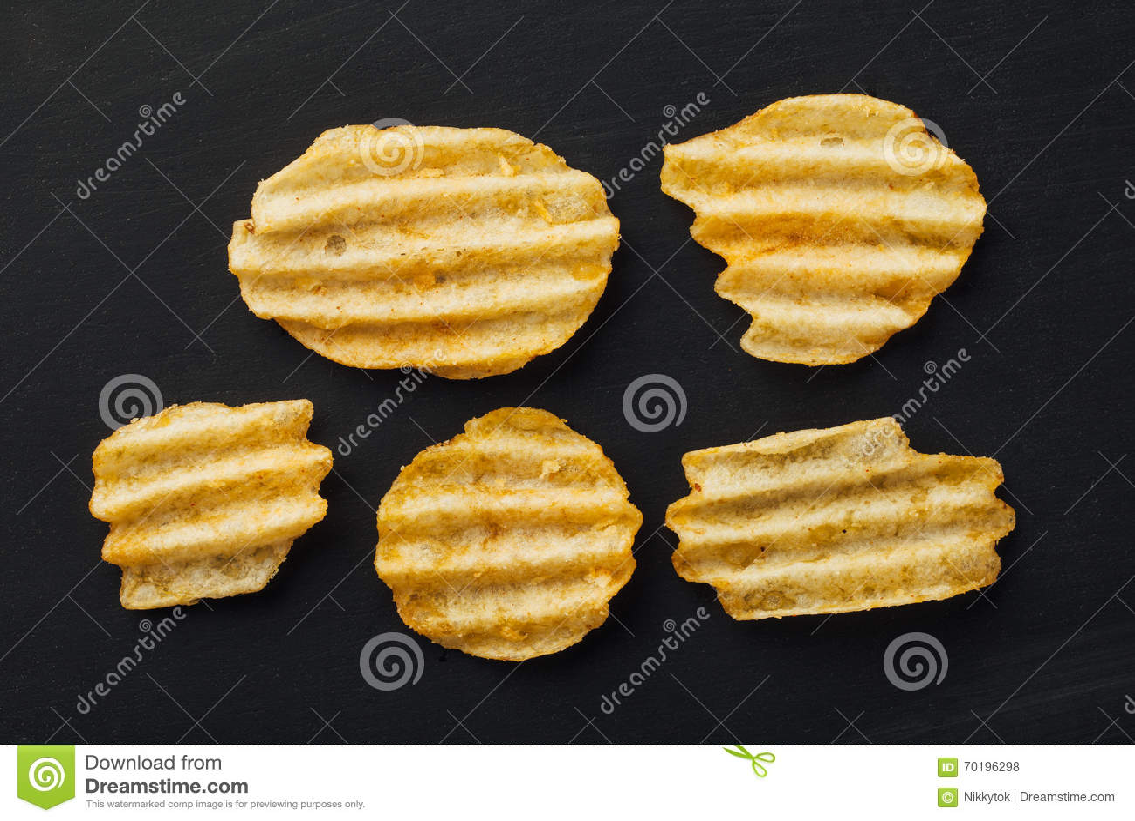 Krusiga potatischiper på svart