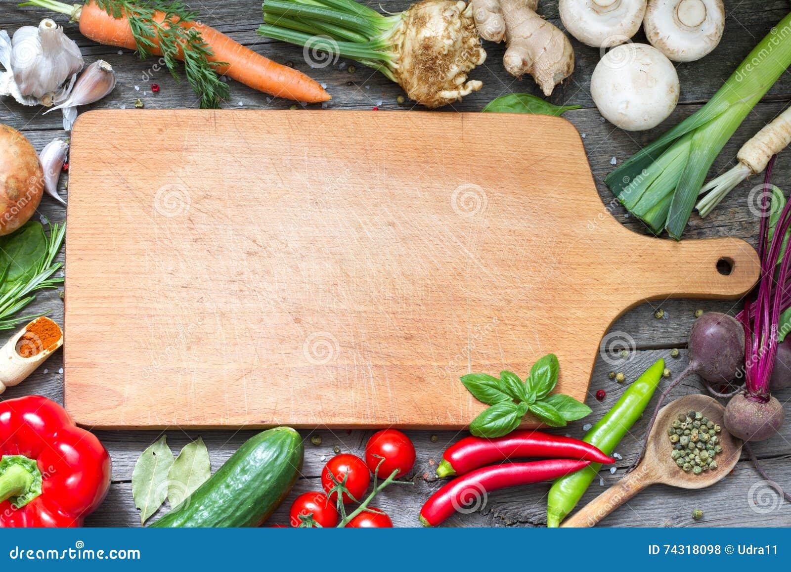 Krydda örter och grönsakmatbakgrund och den tomma skärbrädan