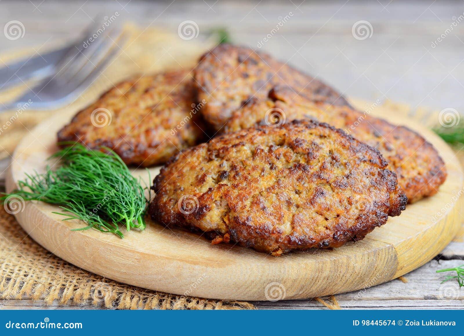 Kryddade pannkakor för feg lever med grönsaker Hem- pannkakor för stekt kycklinglever på ett träbräde För sidomaträtt för feg lev