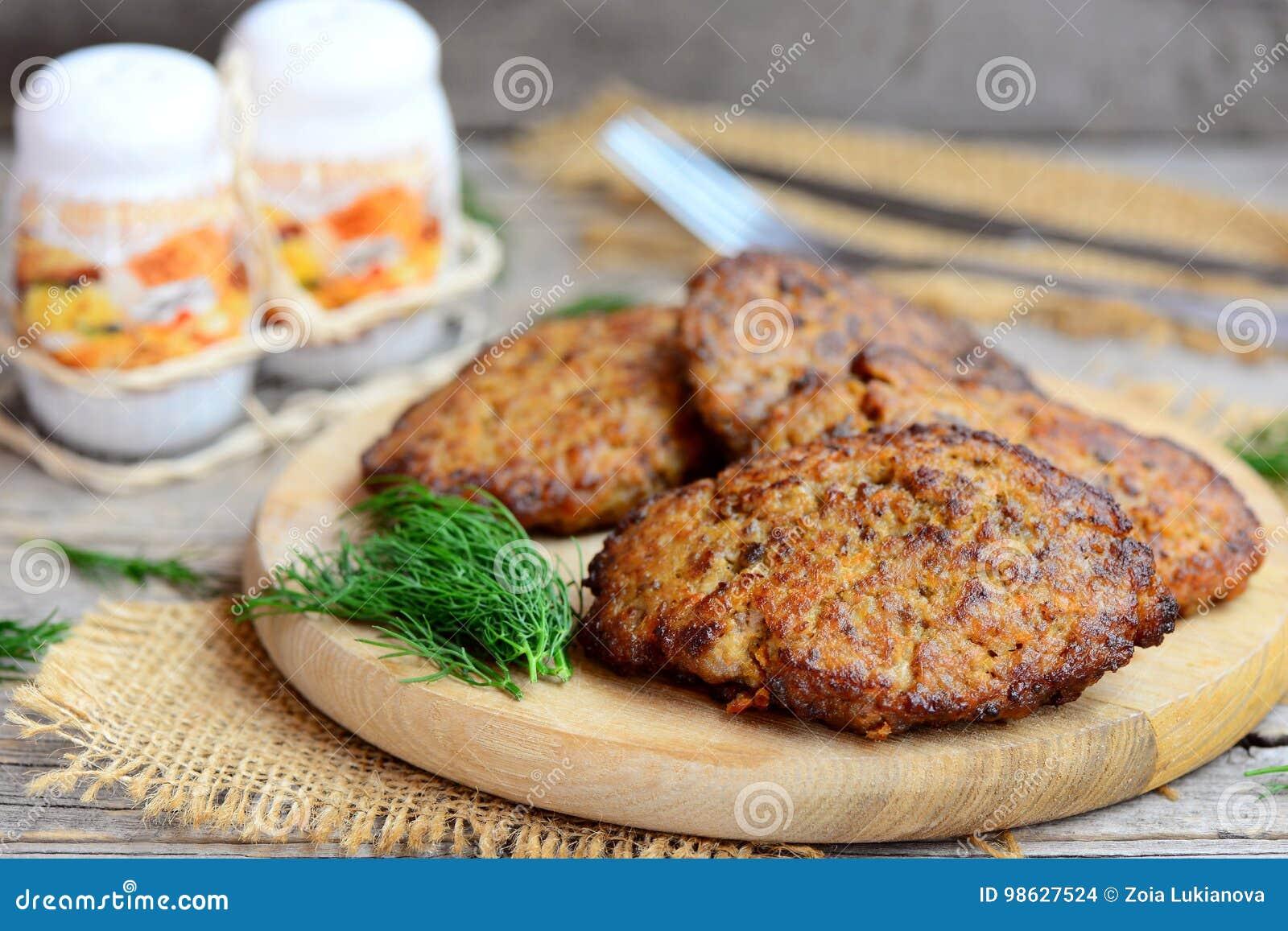 Kryddiga små pastejer för feg lever med grönsaker Bruna små pastejer för stekt kycklinglever på en träskärbräda