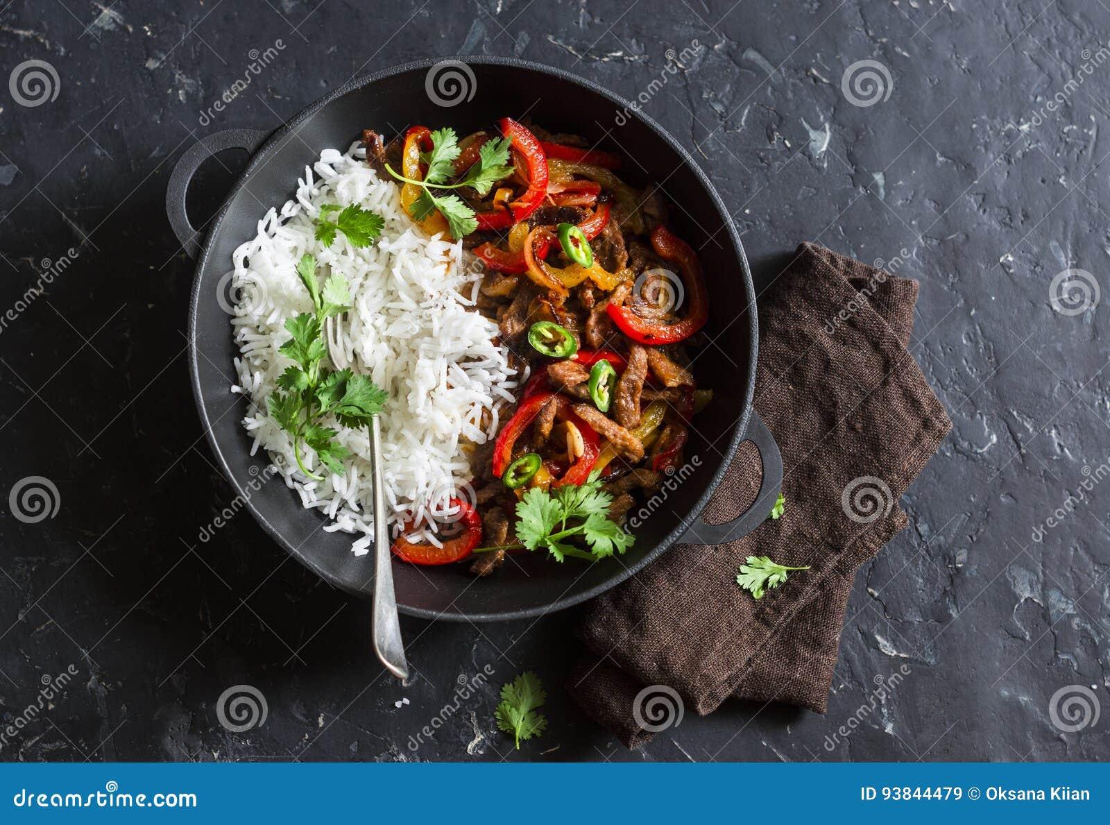 Kryddigt nötkött med grönsaker och ris i en gjutjärnkastrull på en mörk bakgrund, bästa sikt