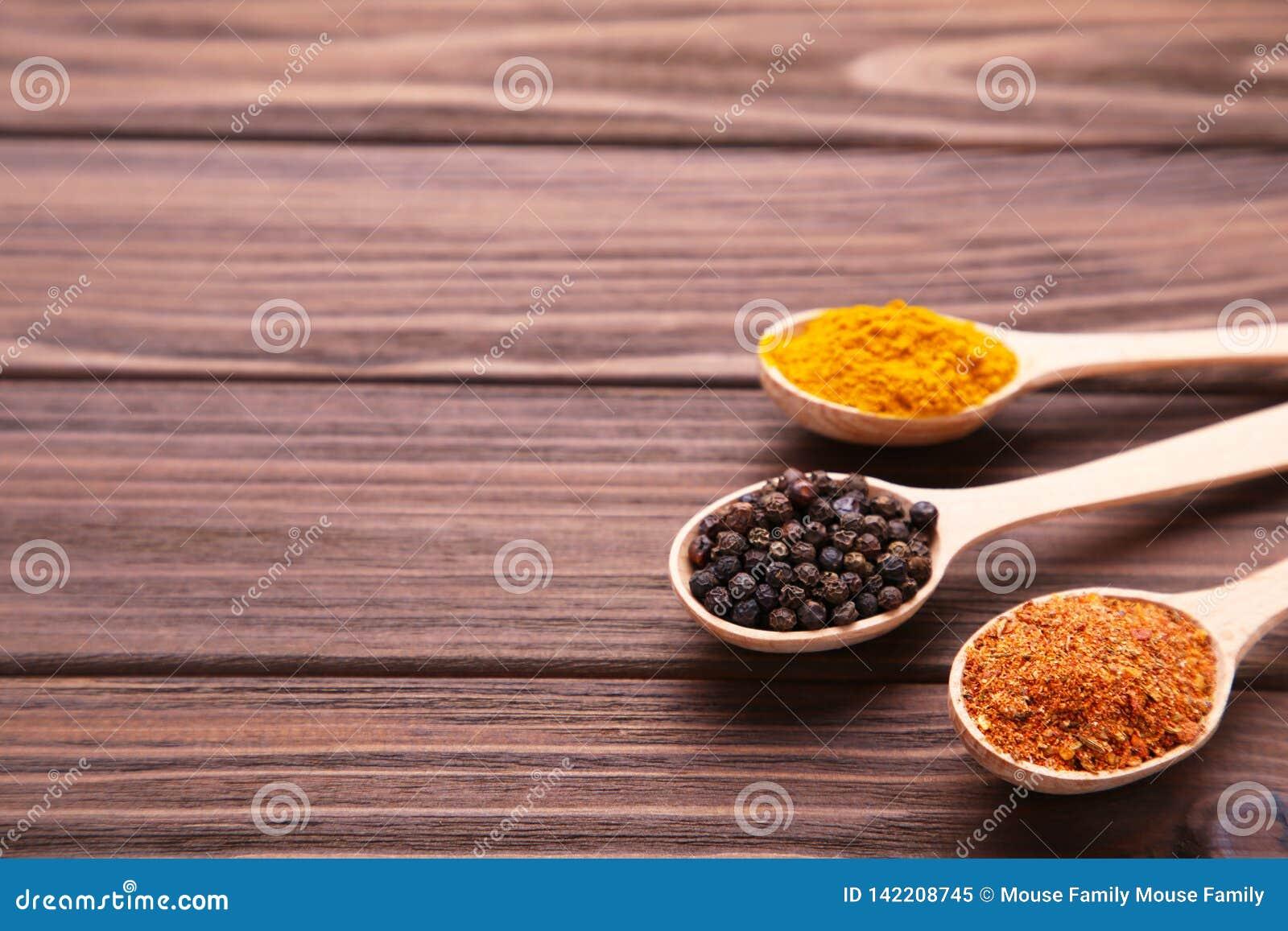 Kryddor blandar i sked på en brun träbakgrund Top beskådar