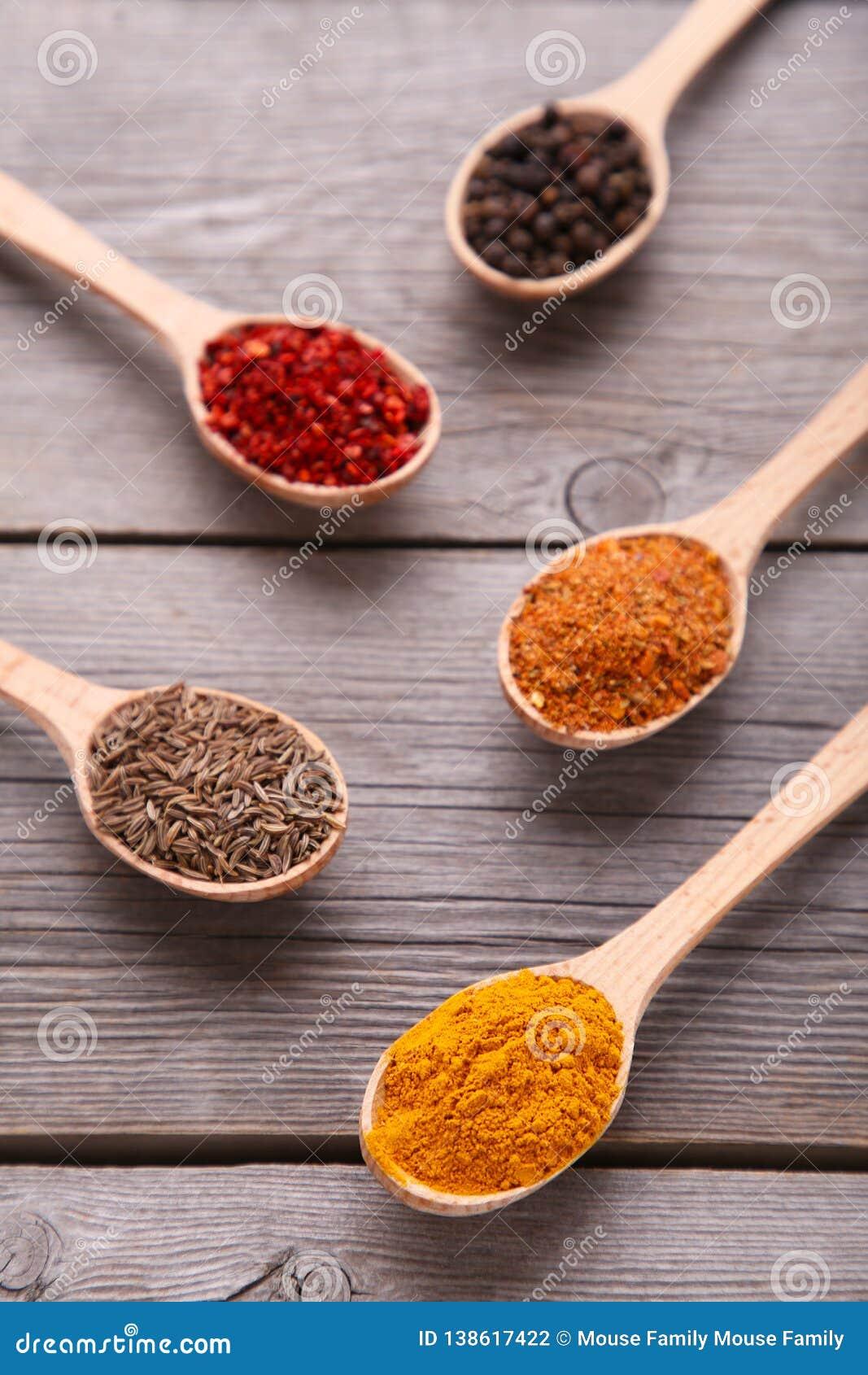 Kryddor blandar på träskedar på en grå träbakgrund Top beskådar
