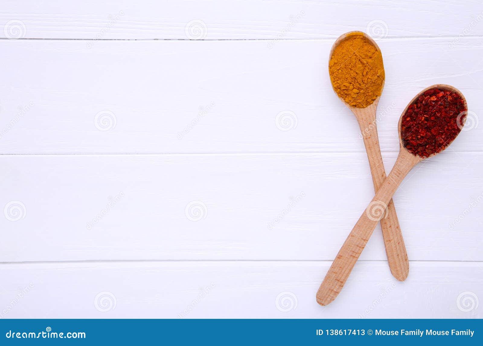 Kryddor blandar på träskedar på en vit träbakgrund Top beskådar