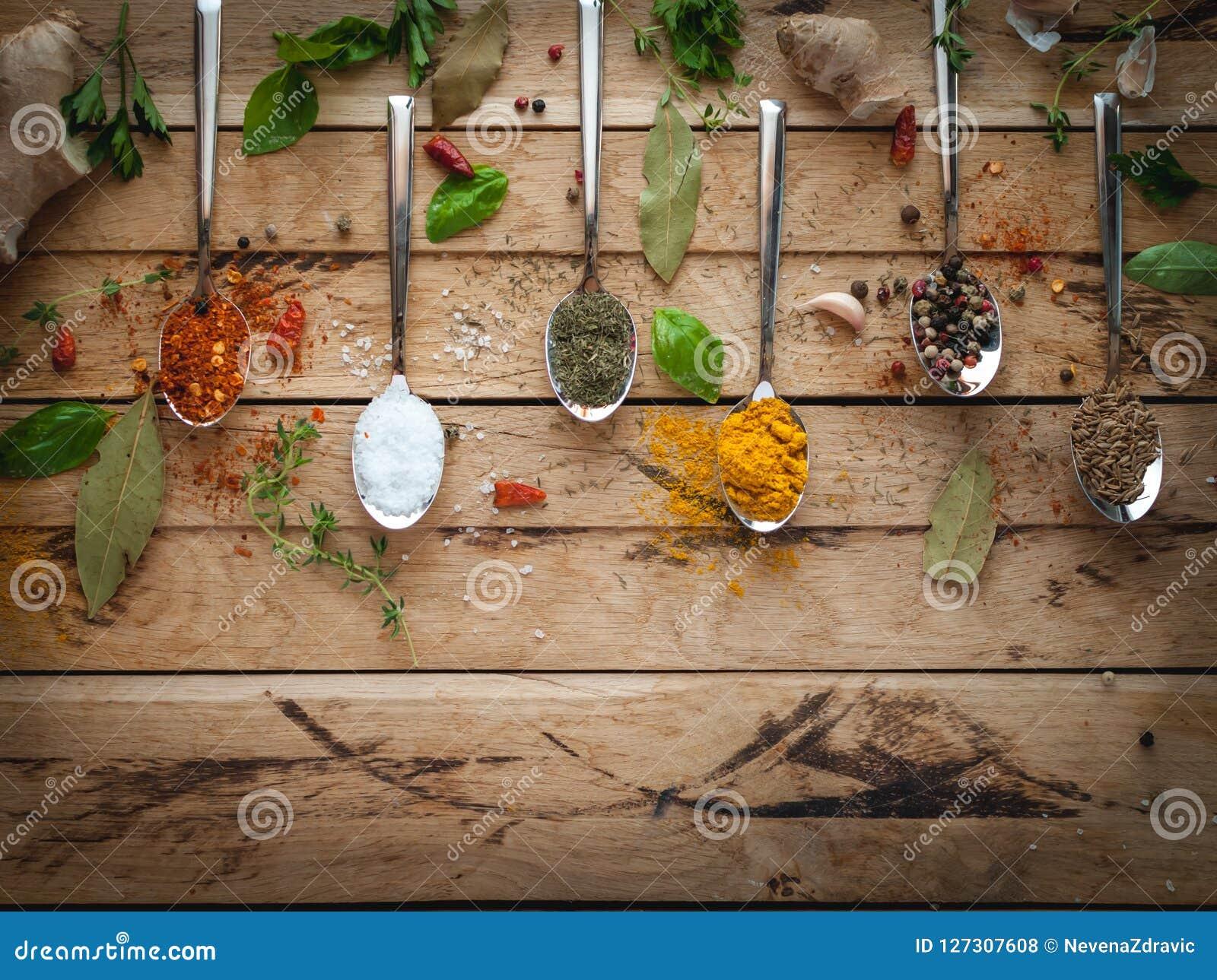 Kryddor och örter i skedar på träbakgrund, bästa sikt