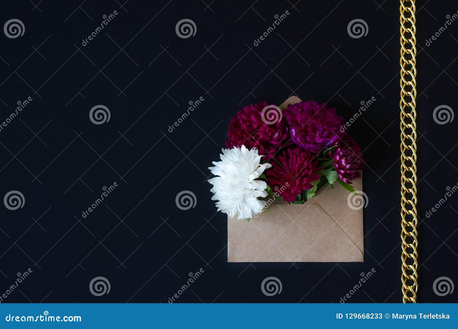 Krysantemumblommor i ett kuvert på en svart bakgrund