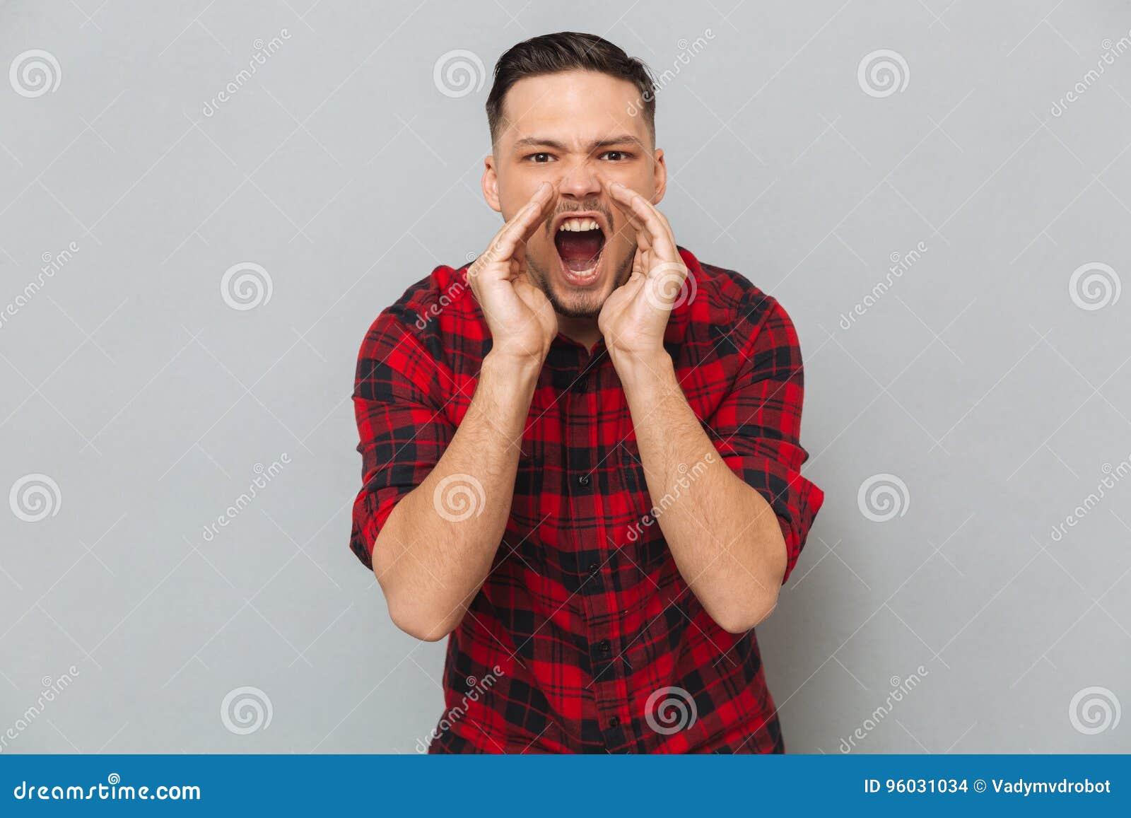 Krzyczący młody człowiek patrzeje kamerę