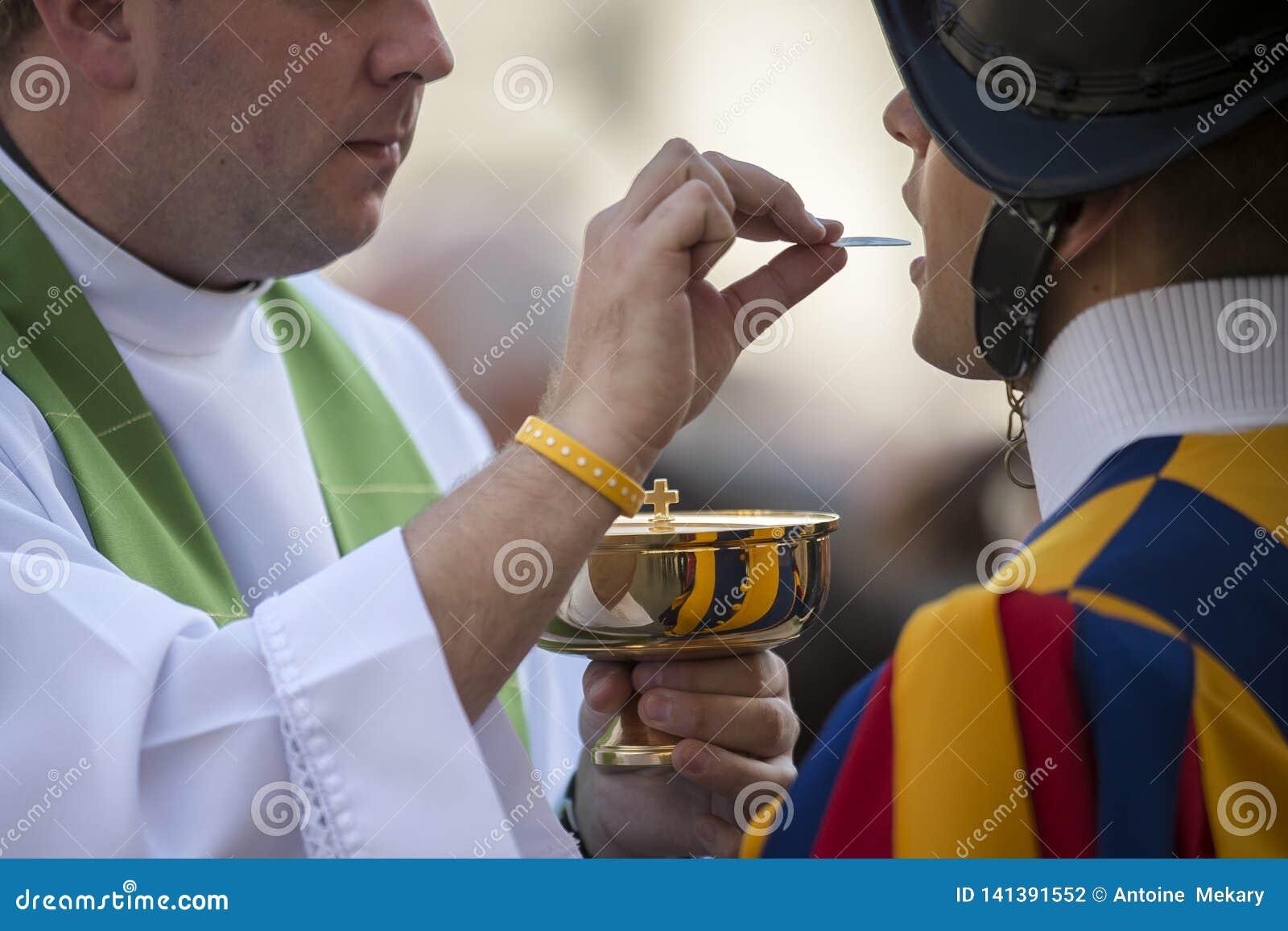 Ksiądz katolicki daje Szwajcarskiemu strażnikowi Świętej komuni