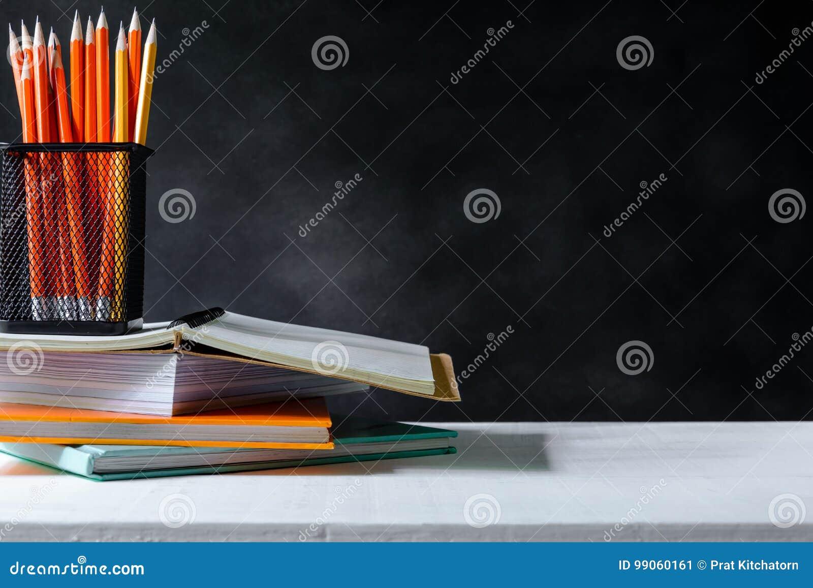 Książka i ołówek na bielu stołu czerni wsiadamy tło z nauką
