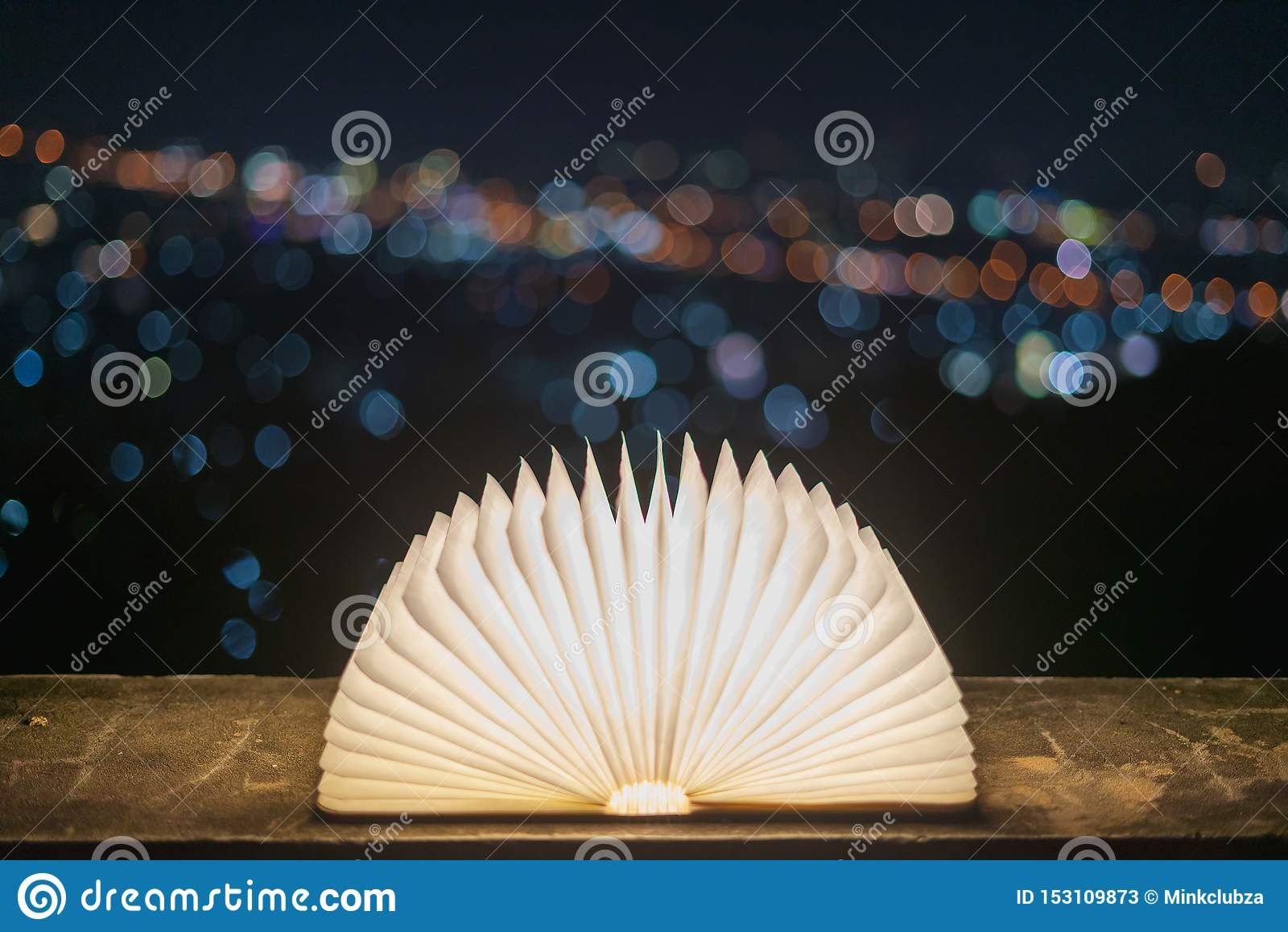 Książka umieszczająca na cementowej podłodze z bokeh tłem dla bożych narodzeń która otwiera z światłem na papierze jak magia, W p