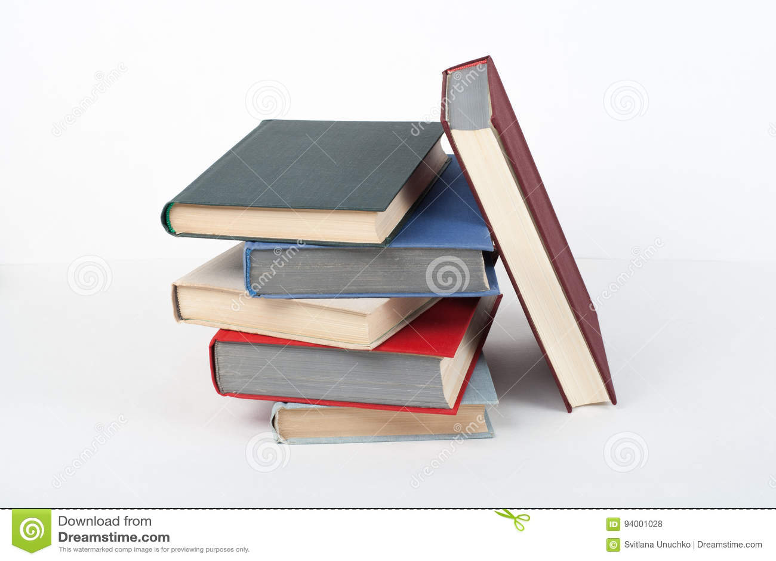 Książkowa sterta, hardback kolorowe książki na drewnianym stole, biały tło tylna szkoły Odbitkowa przestrzeń dla teksta Edukacja